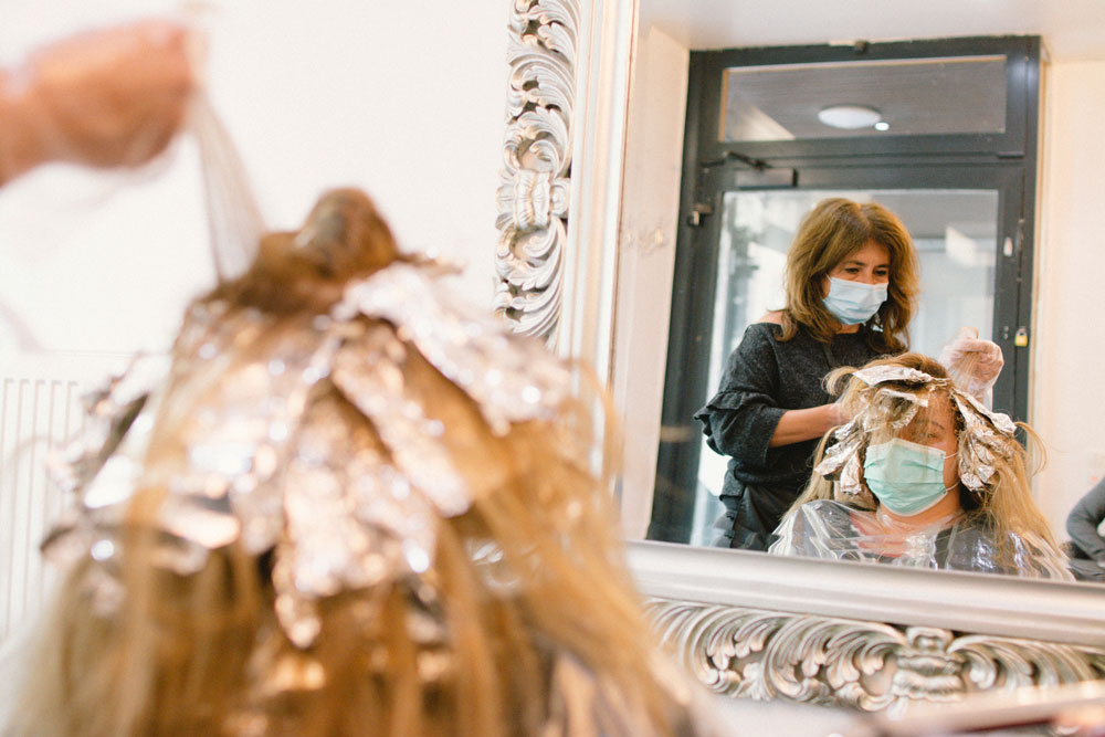 A hairdresser styles her client's hair at her salon on the first day of reopening since March because of the coronavirus in Cologne, Germany, on May 4.