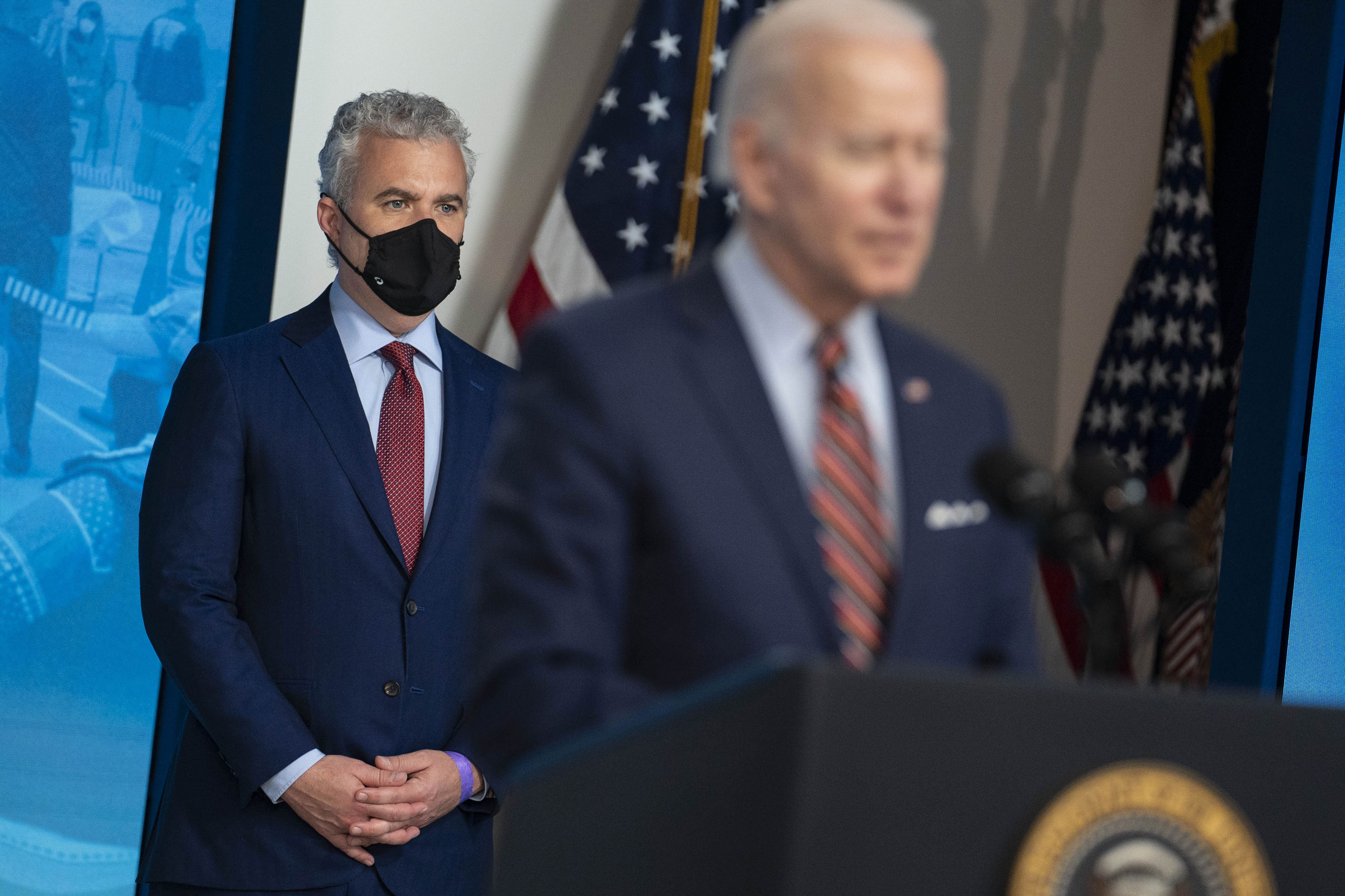Jeff Zients, White House Covid-19 coordinator, left, wears a protective mask while listening as President Joe Biden speaks on Wednesday, April 21.