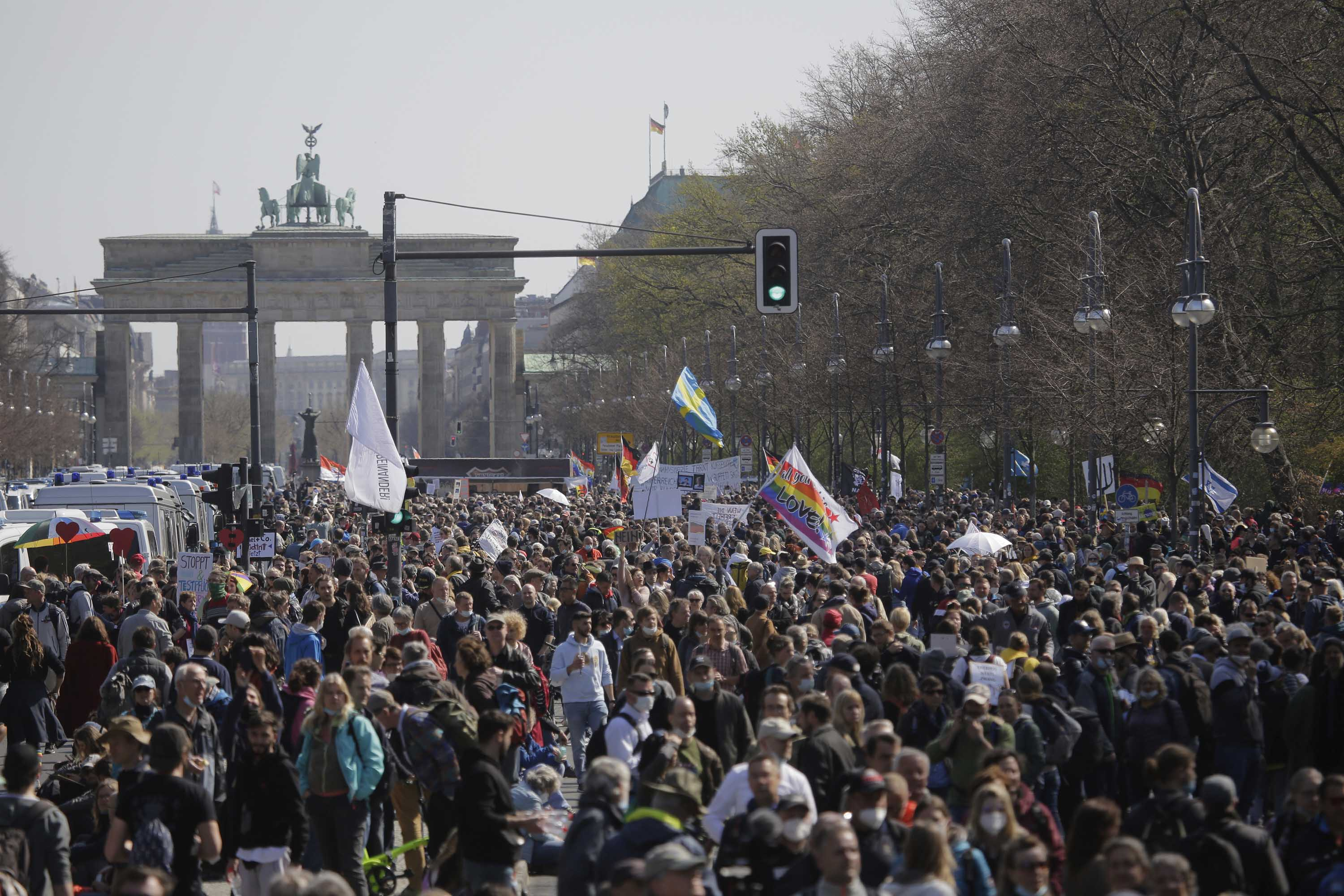Demonstrators attend a protest rally against the government's measures to contain the coronavirus pandemic, near the Brandenburg Gate in Berlin, Germany, on Wednesday, April 21.