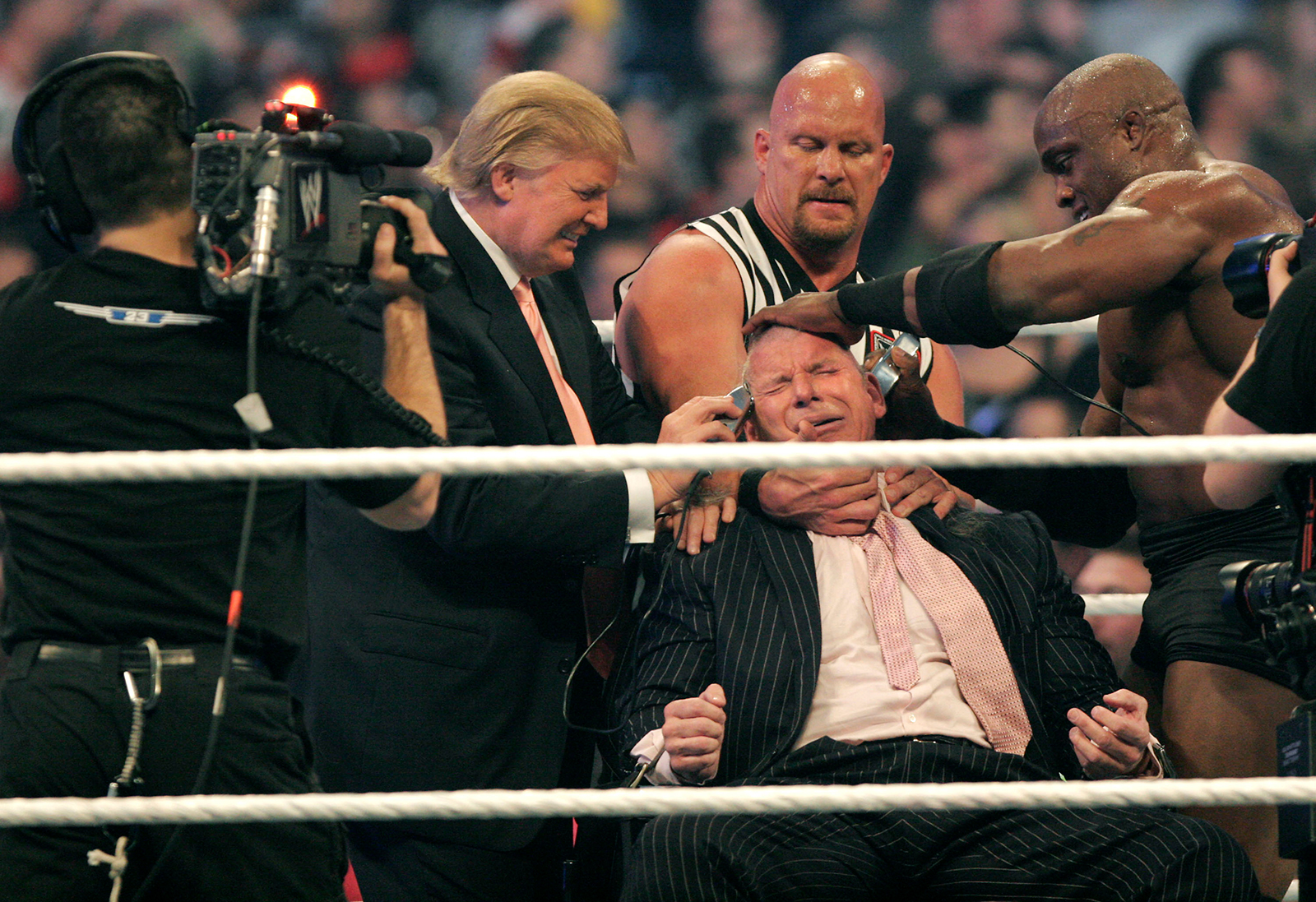 WWE chairman Vince McMahon (center) has his head shaved by Donald Trump and Bobby Lashley (right) while being held down by ''Stone Cold'' Steve Austin after losing a bet in the Battle of the Billionaires at the 2007 World Wrestling Entertainment's Wrestlemania at Ford Field in Detroit, Michigan, on April 1, 2007.