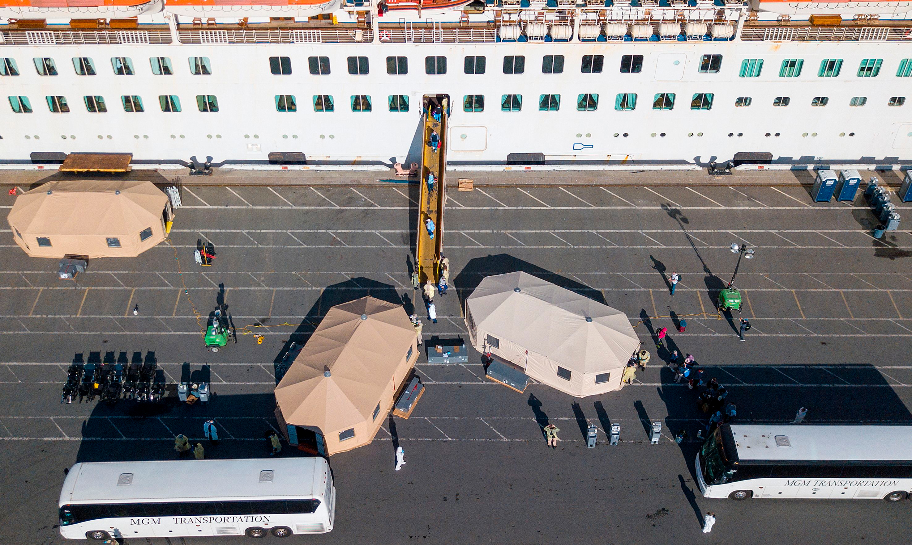 Passengers are disembarked from the Grand Princess cruise ship at the Port of Oakland in Oakland, California on March 10, 2020.