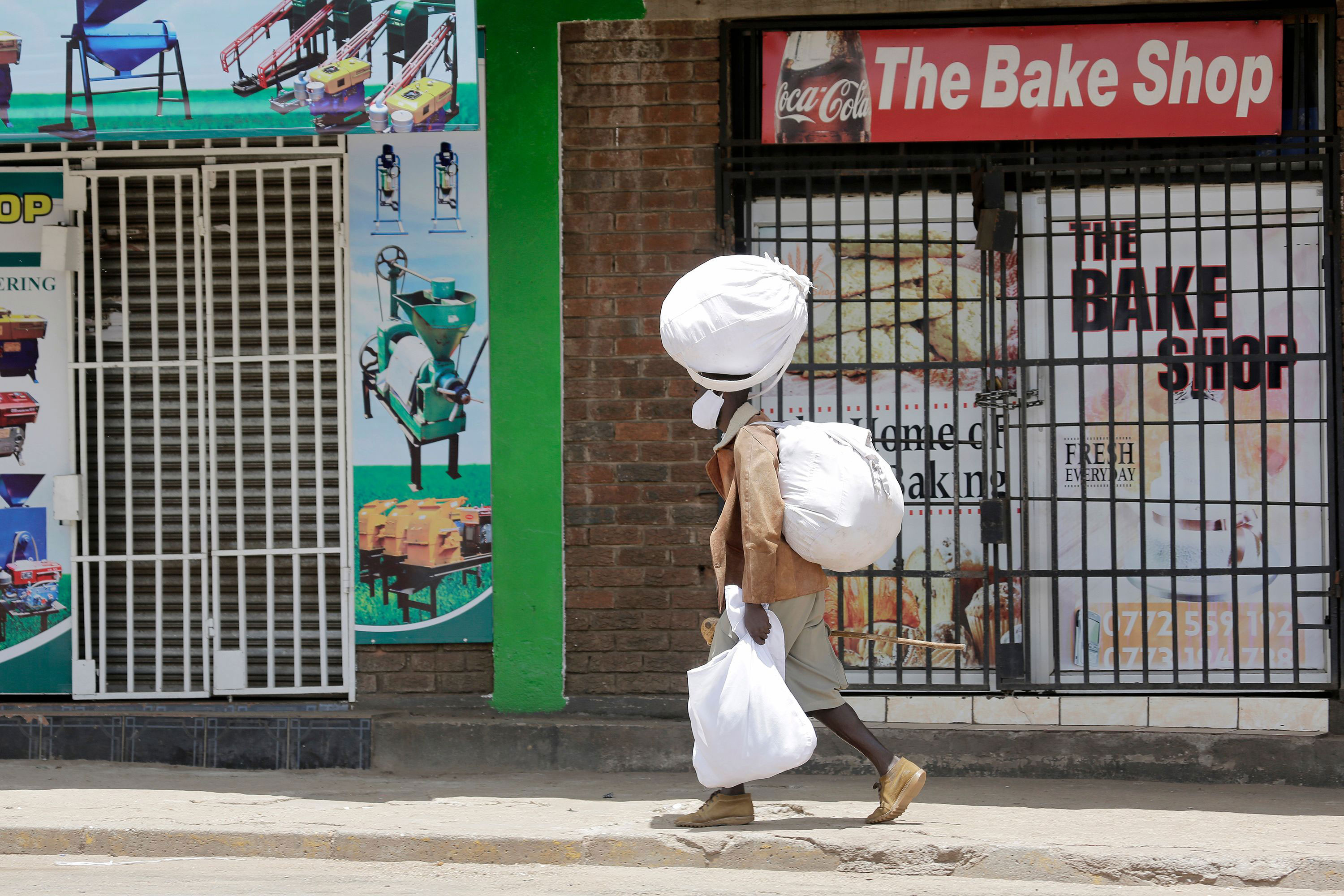 A person passes closed shops in downtown Harare, Zimbabwe, on January 5.