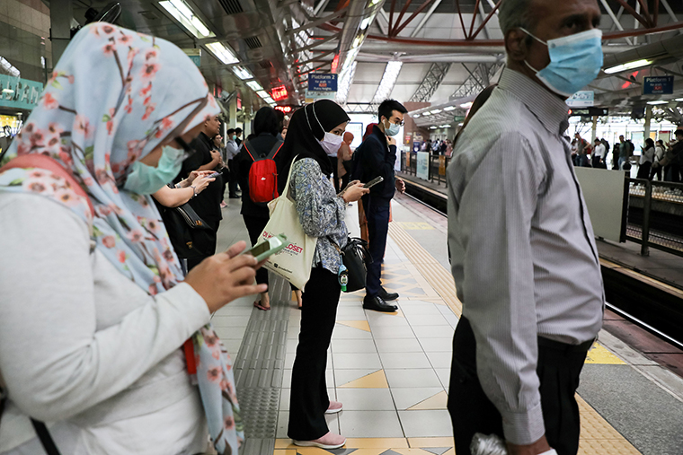 Passengers wear protective masks while they wait for a train, following the outbreak of the new coronavirus in China, in Kuala Lumpur, Malaysia, on February 10.