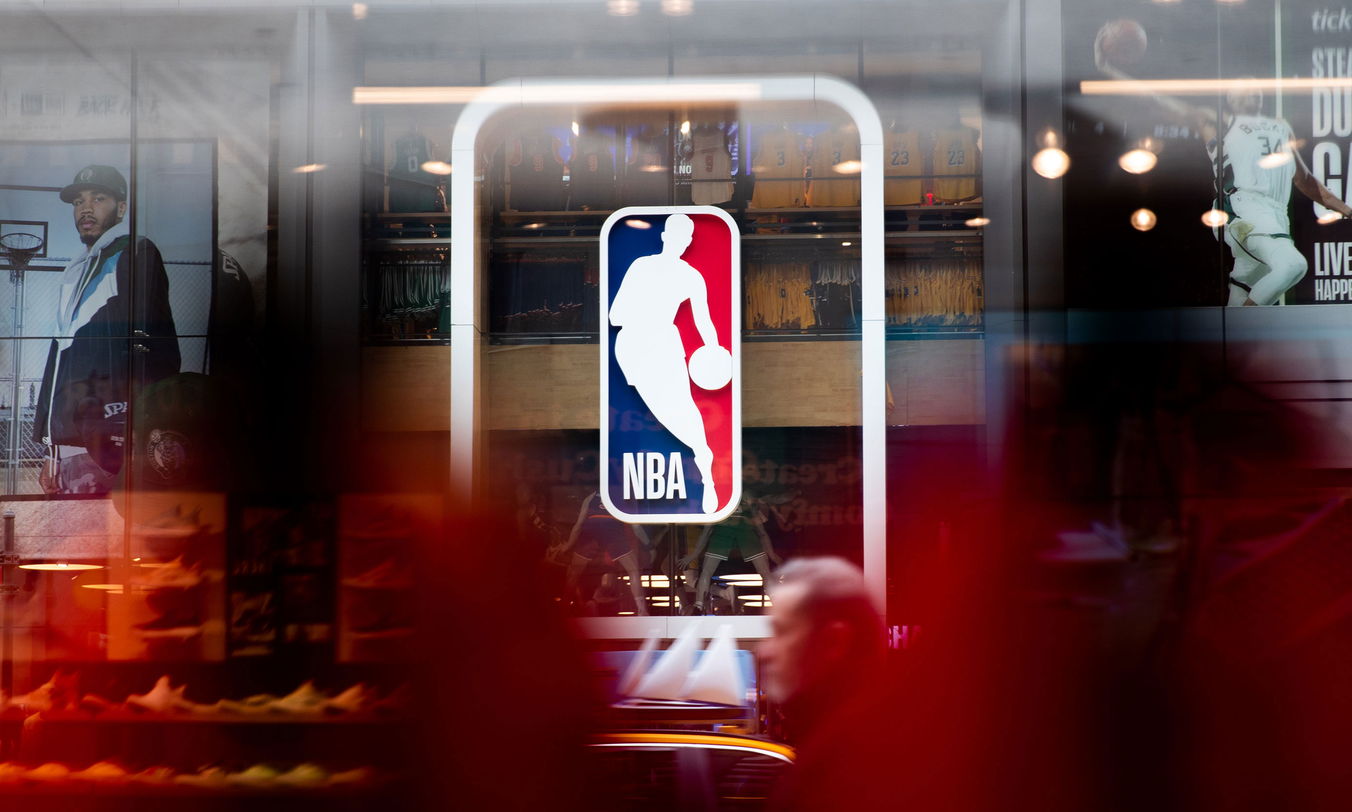 Pedestrians walk past an NBA store on March 12 in New York City.
