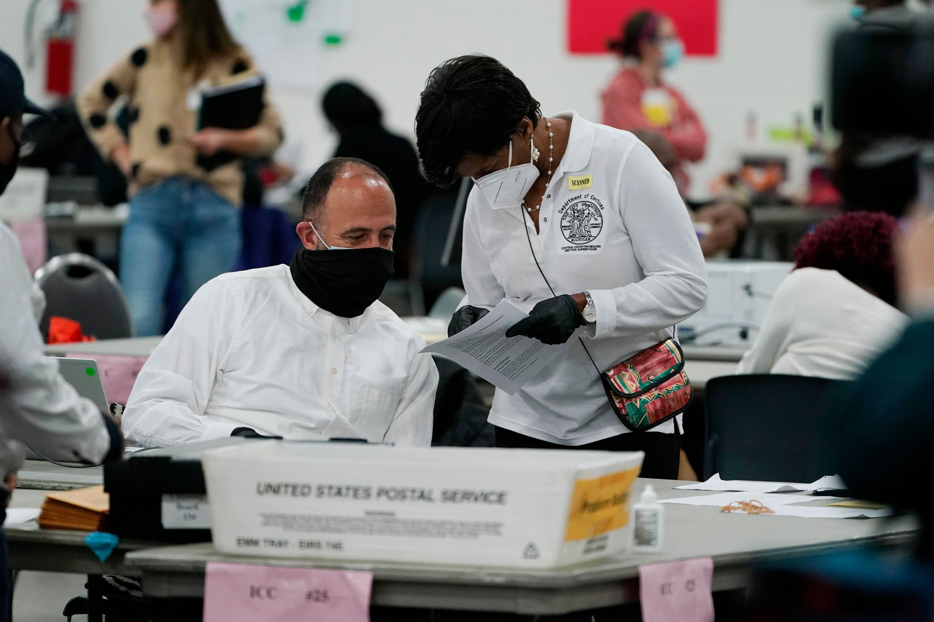 A worker checks with an election supervisor at the central counting board in Detroit on November 4.
