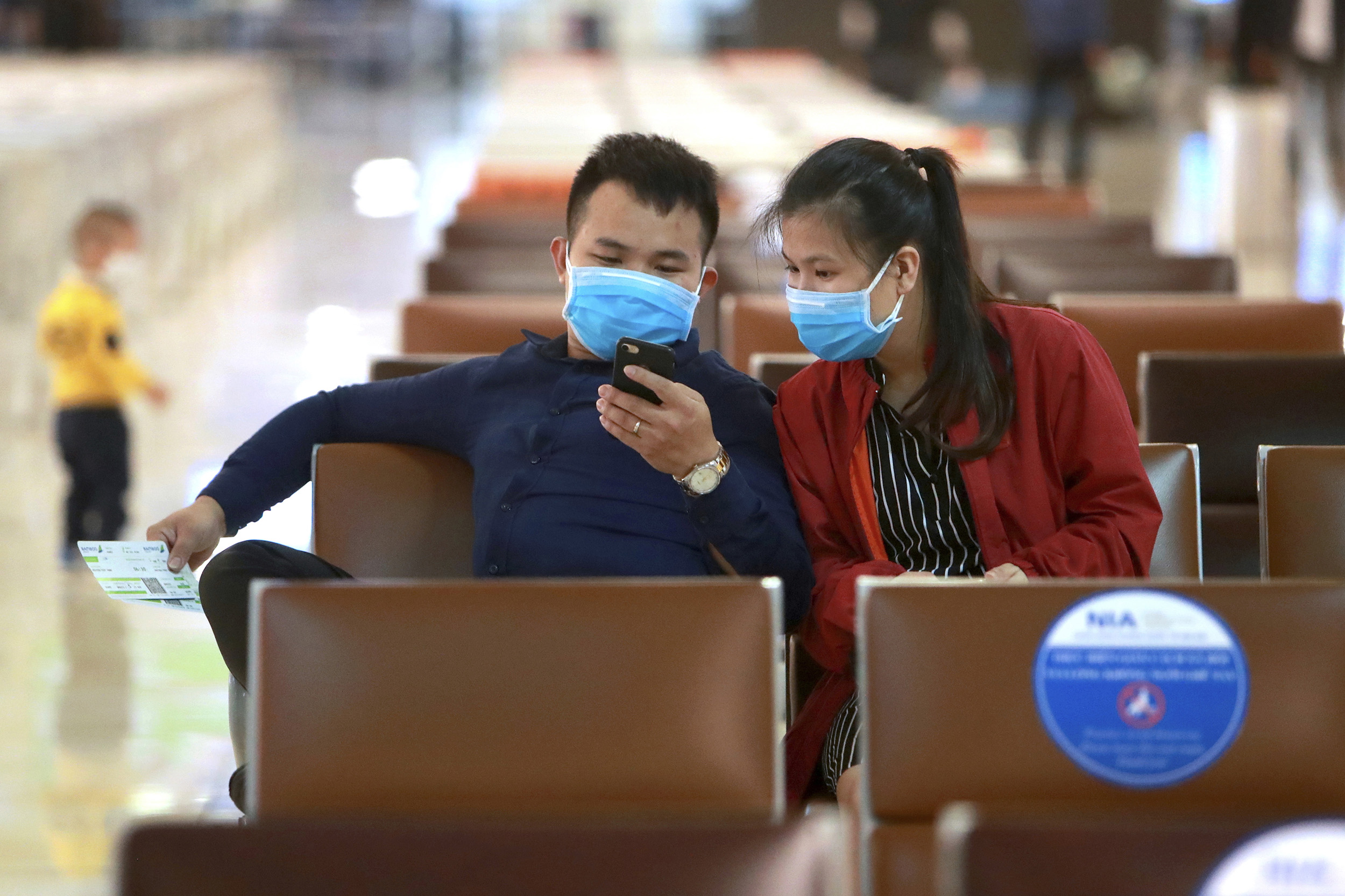 Passengers sit at a departure lounge at Hanoi airport in Hanoi, Vietnam, on Thursday, May 7.