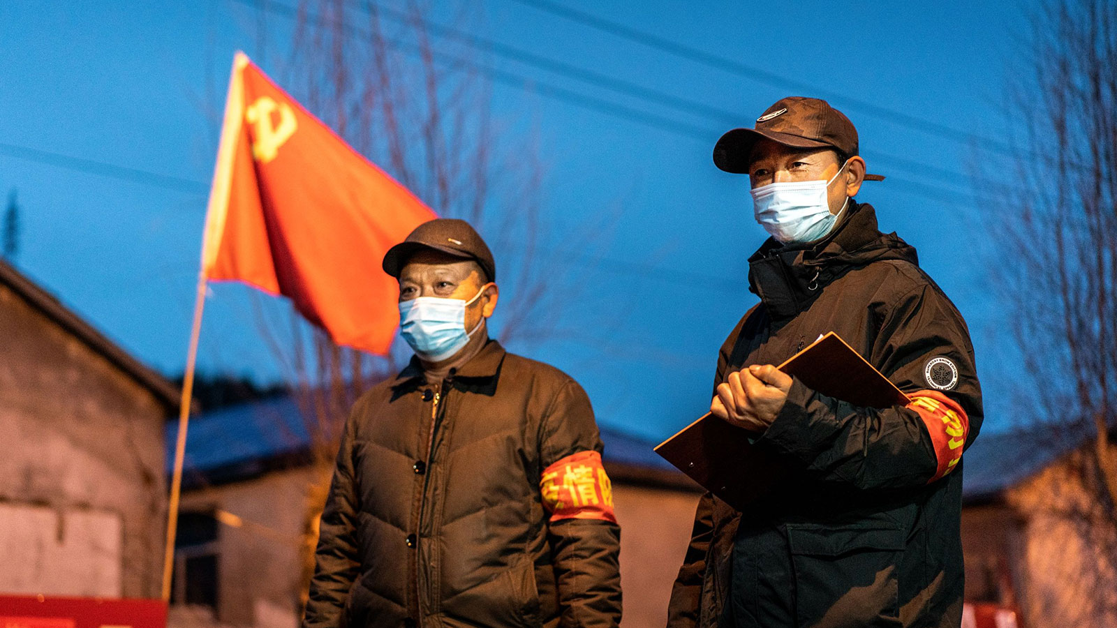 This photo taken on April 21, 2020 shows officials keeping watch at a checkpoint in the border city of Suifenhe, in China's northeastern Heilongjiang province. A cluster of coronavirus cases in the provincial capital Harbin has forced officials to tighten restrictions on movement.