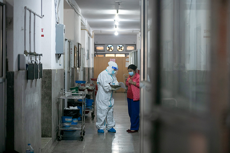 A health worker is seen inside the COVID_19 ward while speaking to a patient's relative at Shukraraaj Tropical and Infectious Disease Hospital in Kathmandu, on April 26.