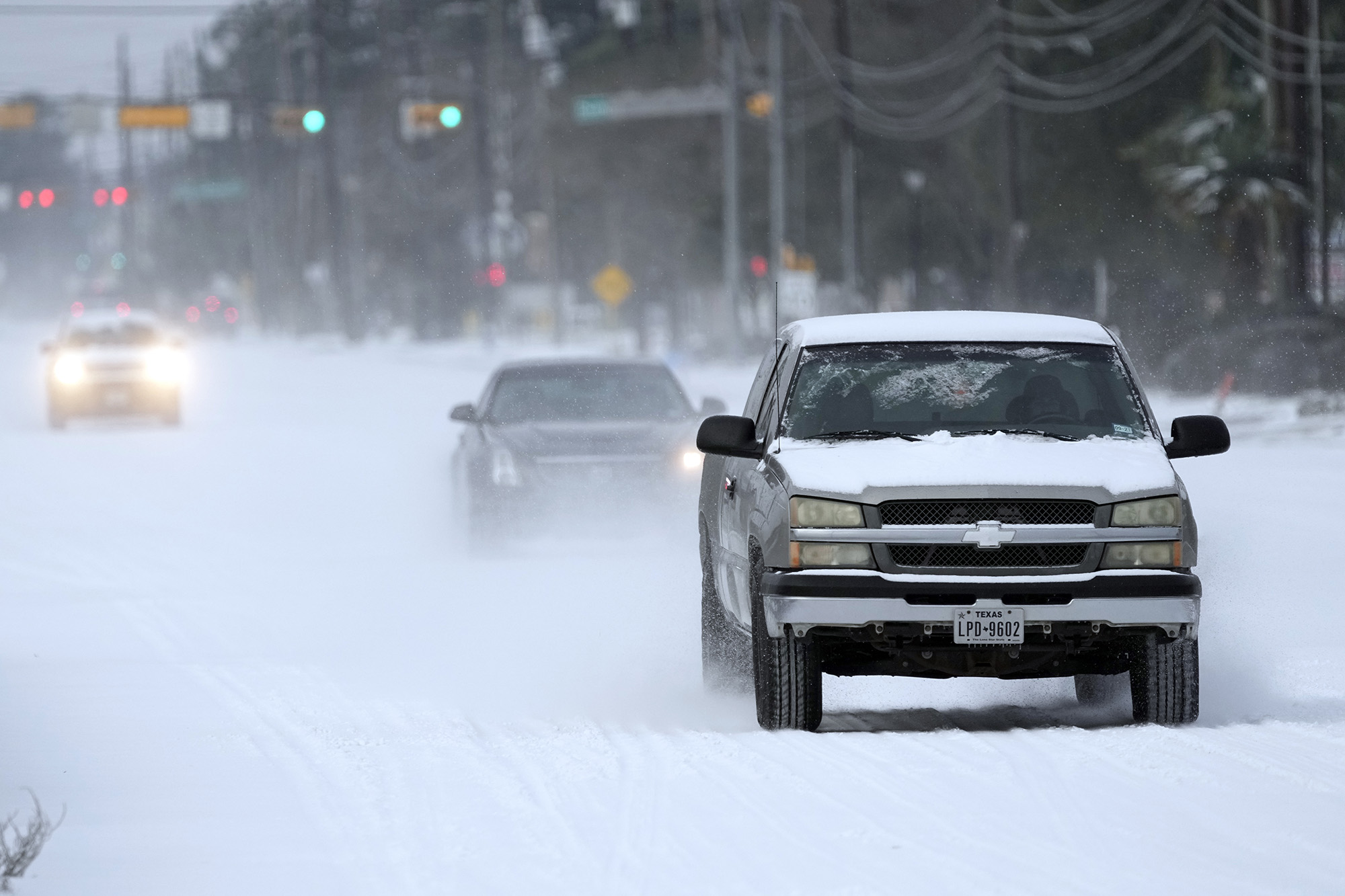 Vehicles drive on snow and sleet-covered roads on Monday, Feb. 15, 2021, in Spring, Texas.