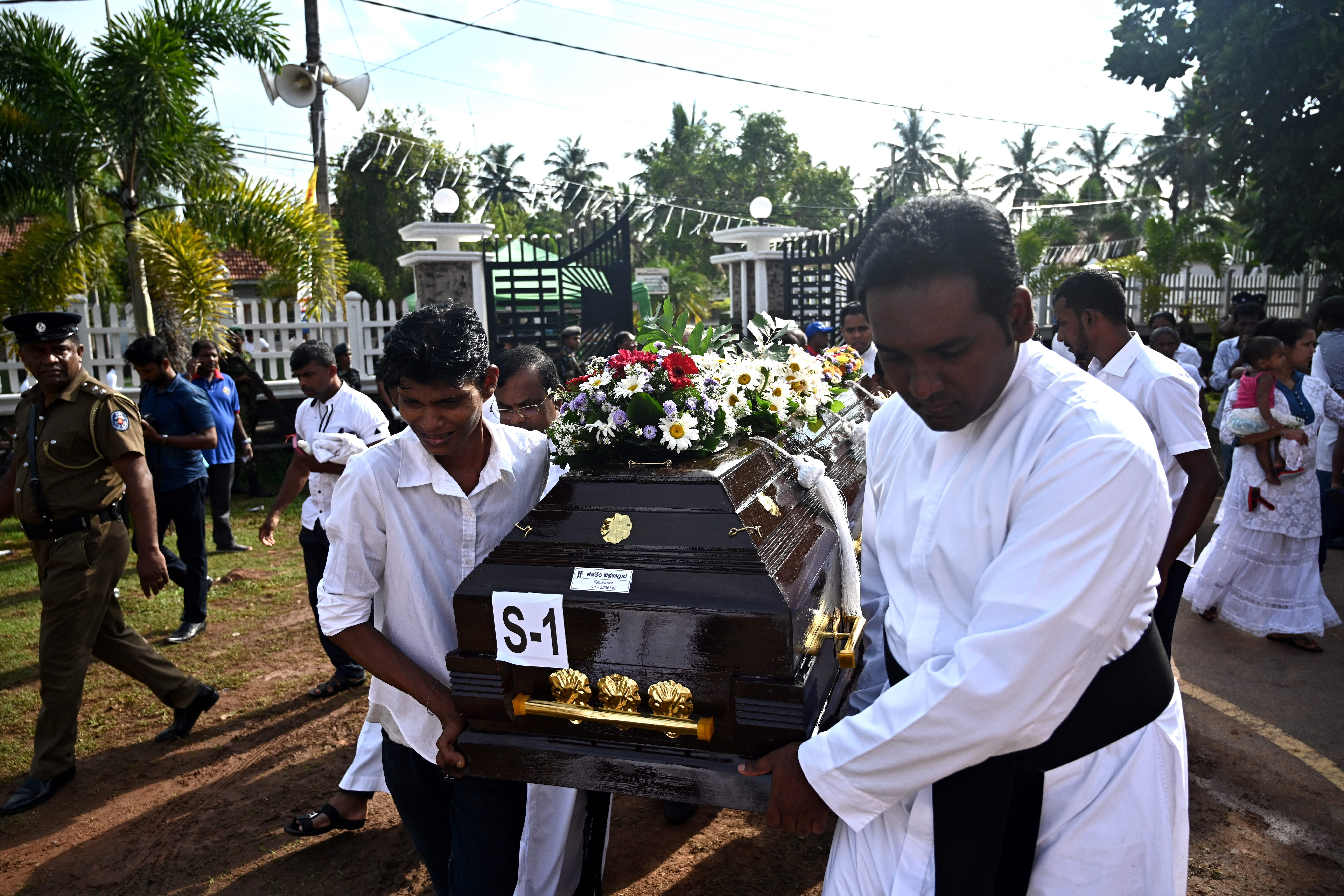 Priests and relatives carry the coffin of a bomb blast victim after a funeral service at St Sebastian's Church in Negombo on Tuesday.