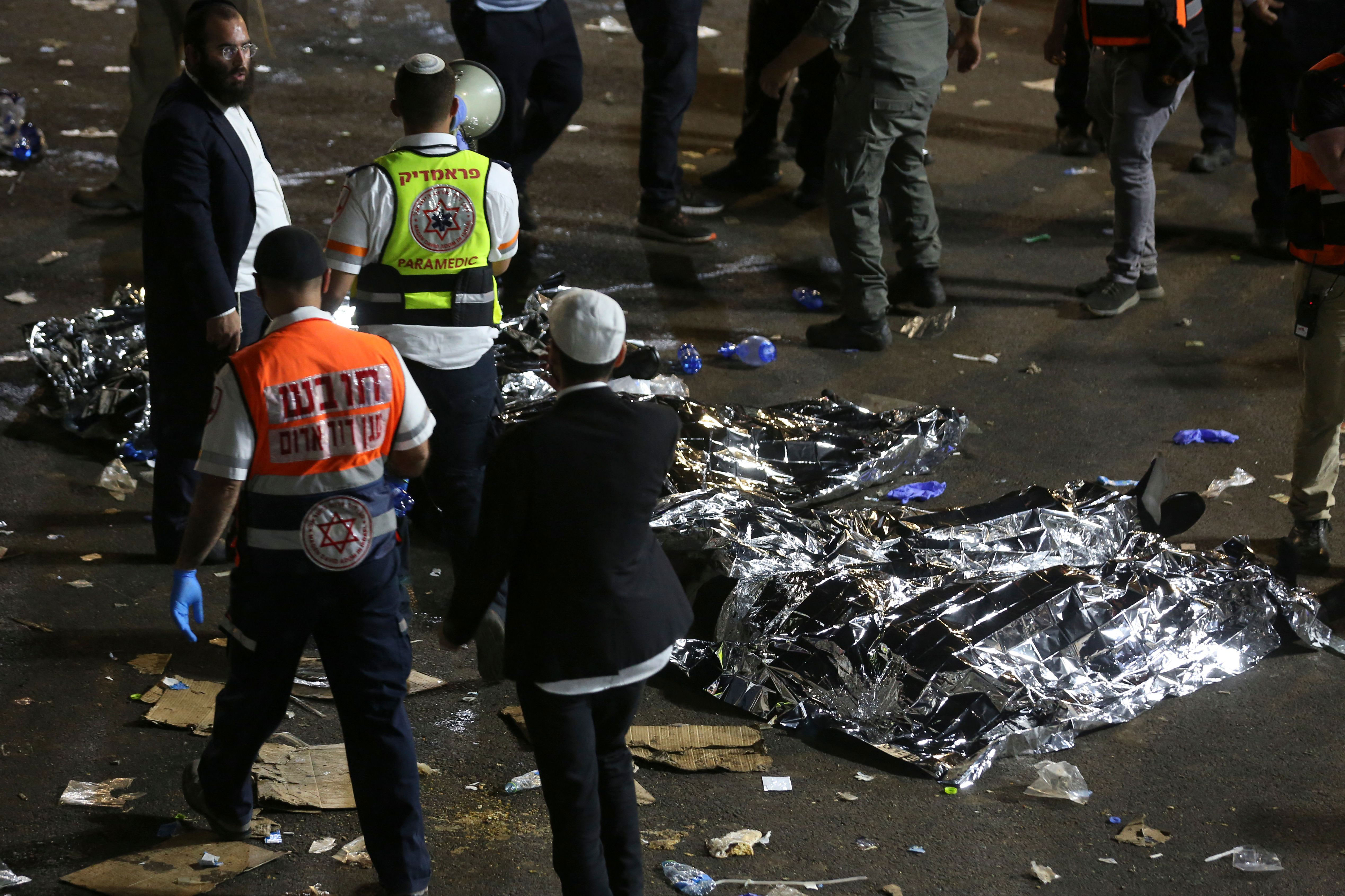 Dozens were killed during a crush at the event; in this photo, paramedics and worshipers stand next to covered bodies in the wake of the disaster.