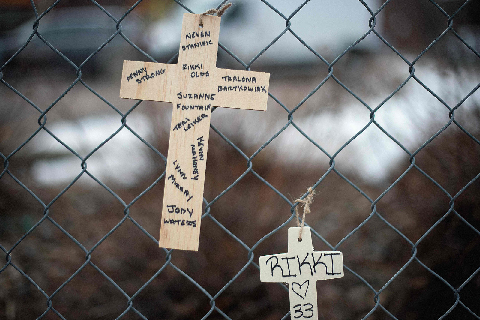 Crosses bearing the names of the shooting victims hang from a fence.