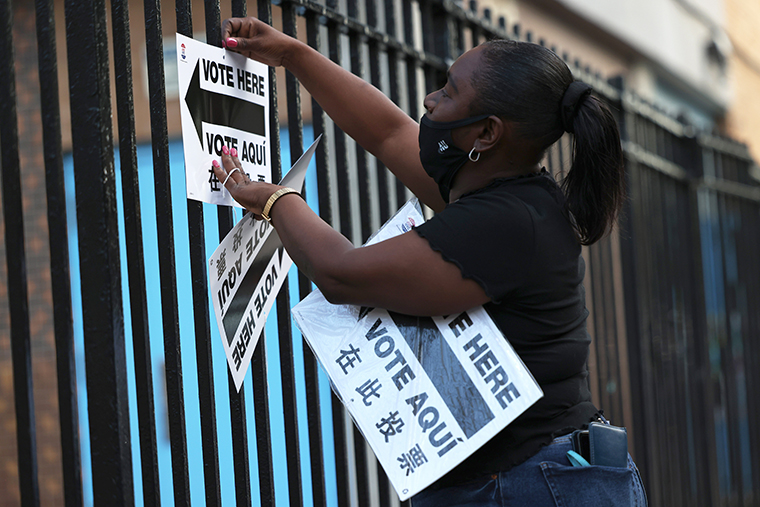 A poll worker hangs up a voting sign during the Primary Election Day at P.S. 81 on June 22, 2021 in the Bedford-Stuyvesant neighborhood of Brooklyn borough in New York City.