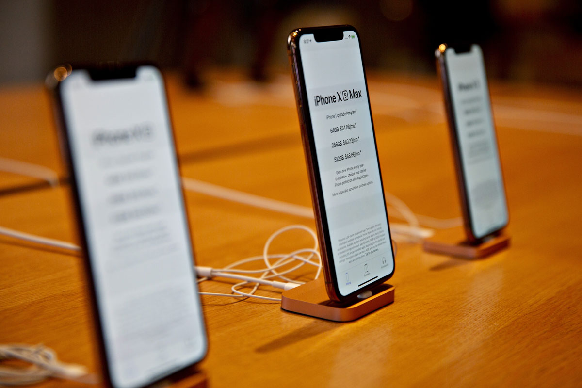 An iPhone XS Max, center, and iPhone XS smartphones sit on display during a sales launch at a store in Chicago, Illinois on Sept. 21, 2018.