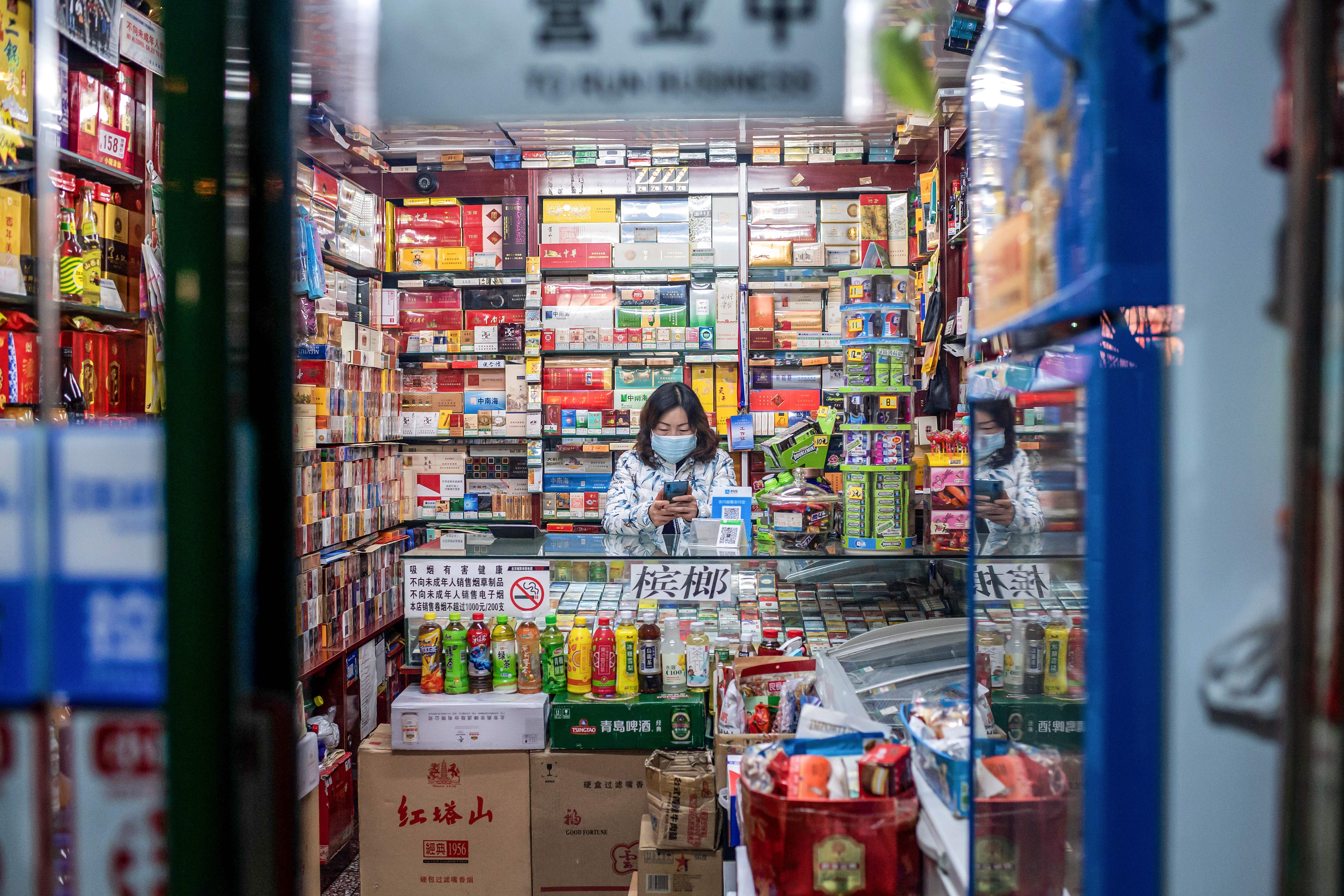 Avendor wearing a protective face mask waits for customers at a shop in Beijing.
