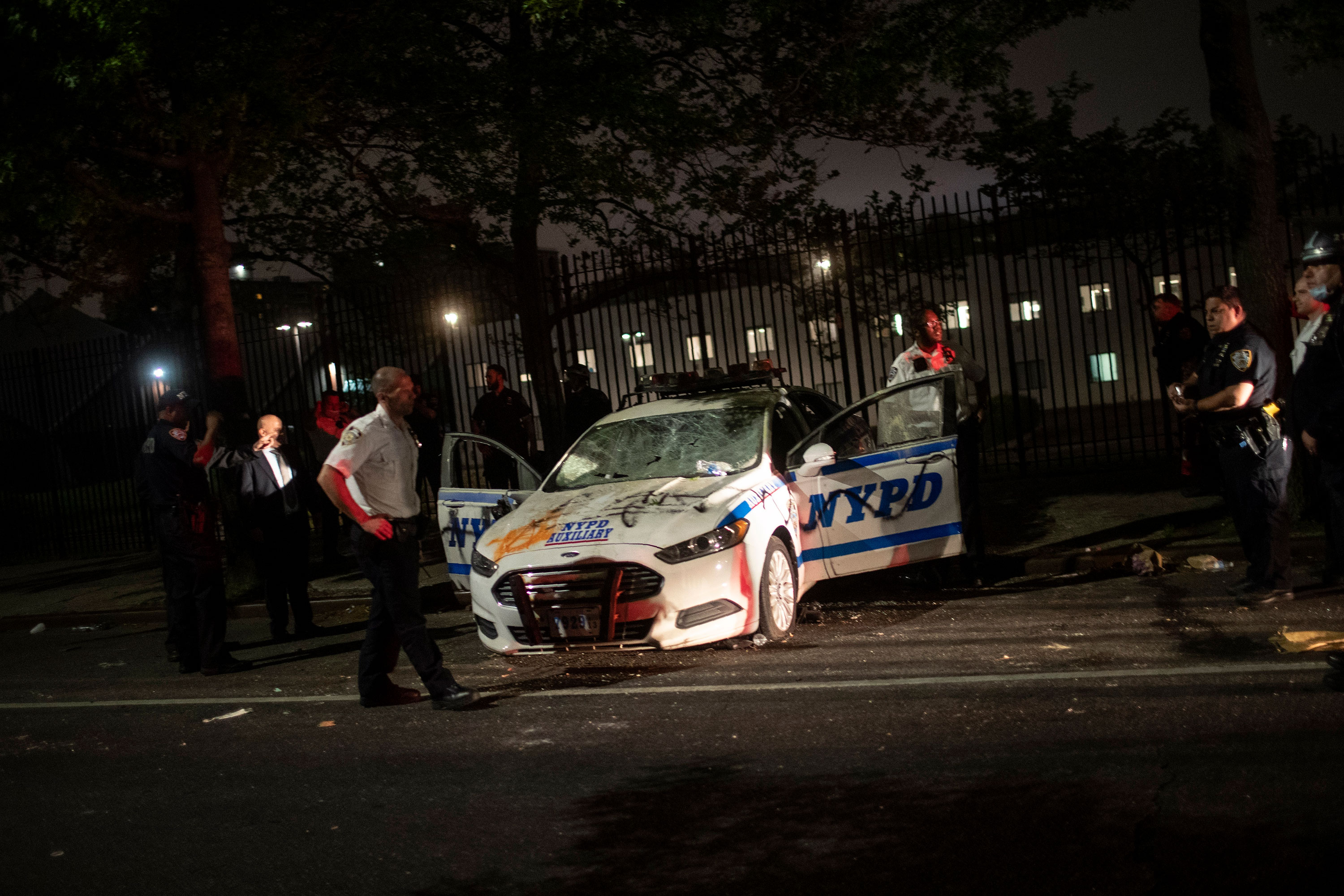 Policemen surround a NYPD vehicle after it was vandalized by protesters in Brooklyn on May 29.