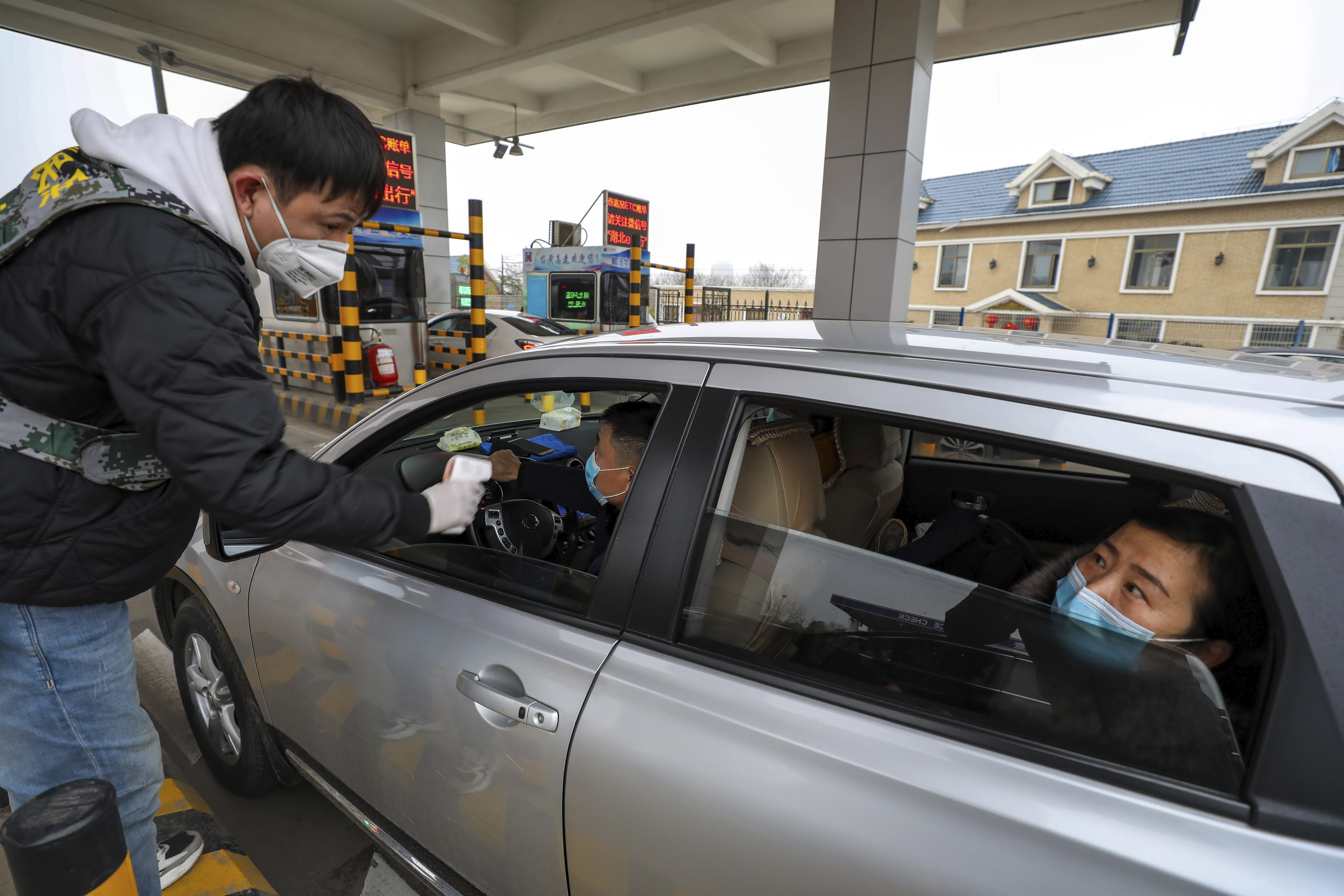 A man uses a thermometer gun to take a driver's temperature at a checkpoint at a highway toll gate in Wuhan on January 23, 2020.
