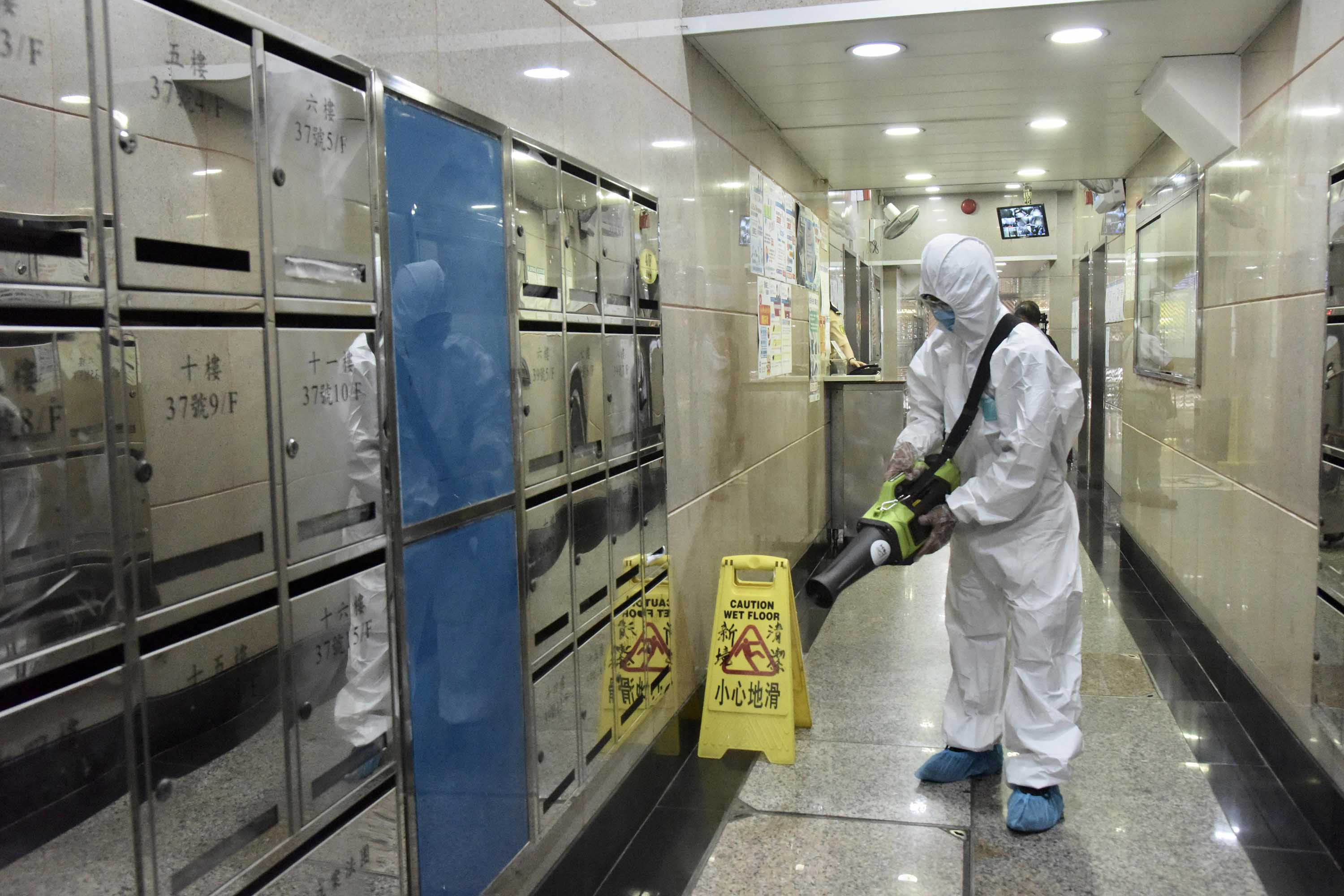 A worker sprays disinfectant at a residential block in Hong Kong on July 8.