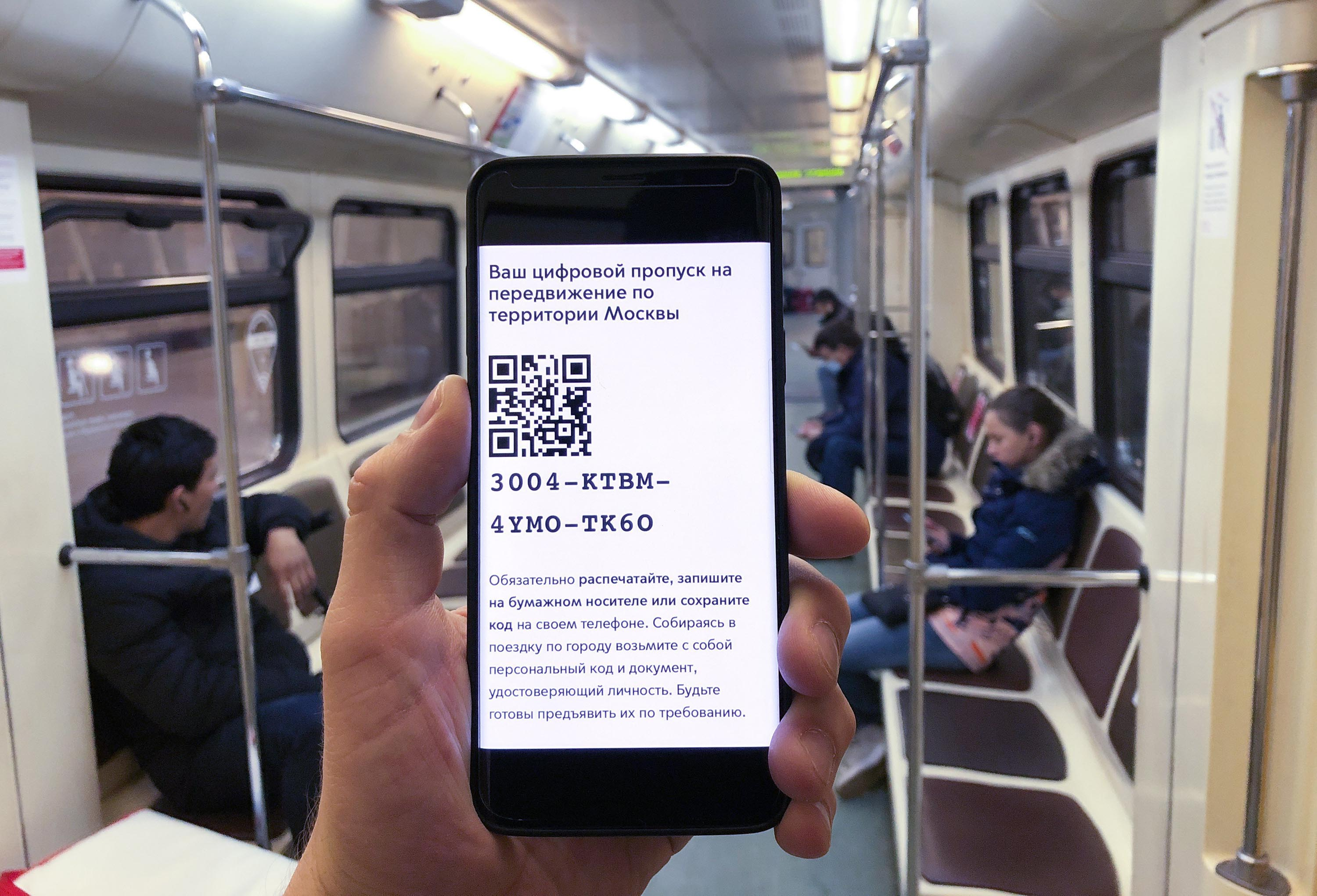 A Moscow metro passenger displays an electronic pass Tuesday with a QR code on a phone.