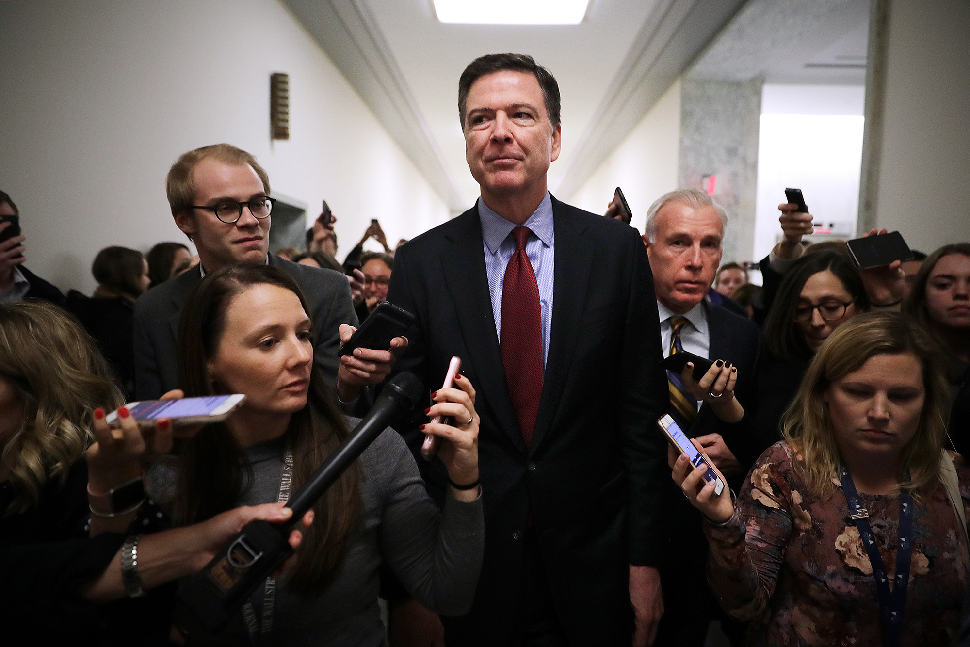 Former Federal Bureau of Investigation Director James Comey is surrounded by reporters after testifying to the House Judiciary and Oversight and Government Reform committees on December 07, 2018