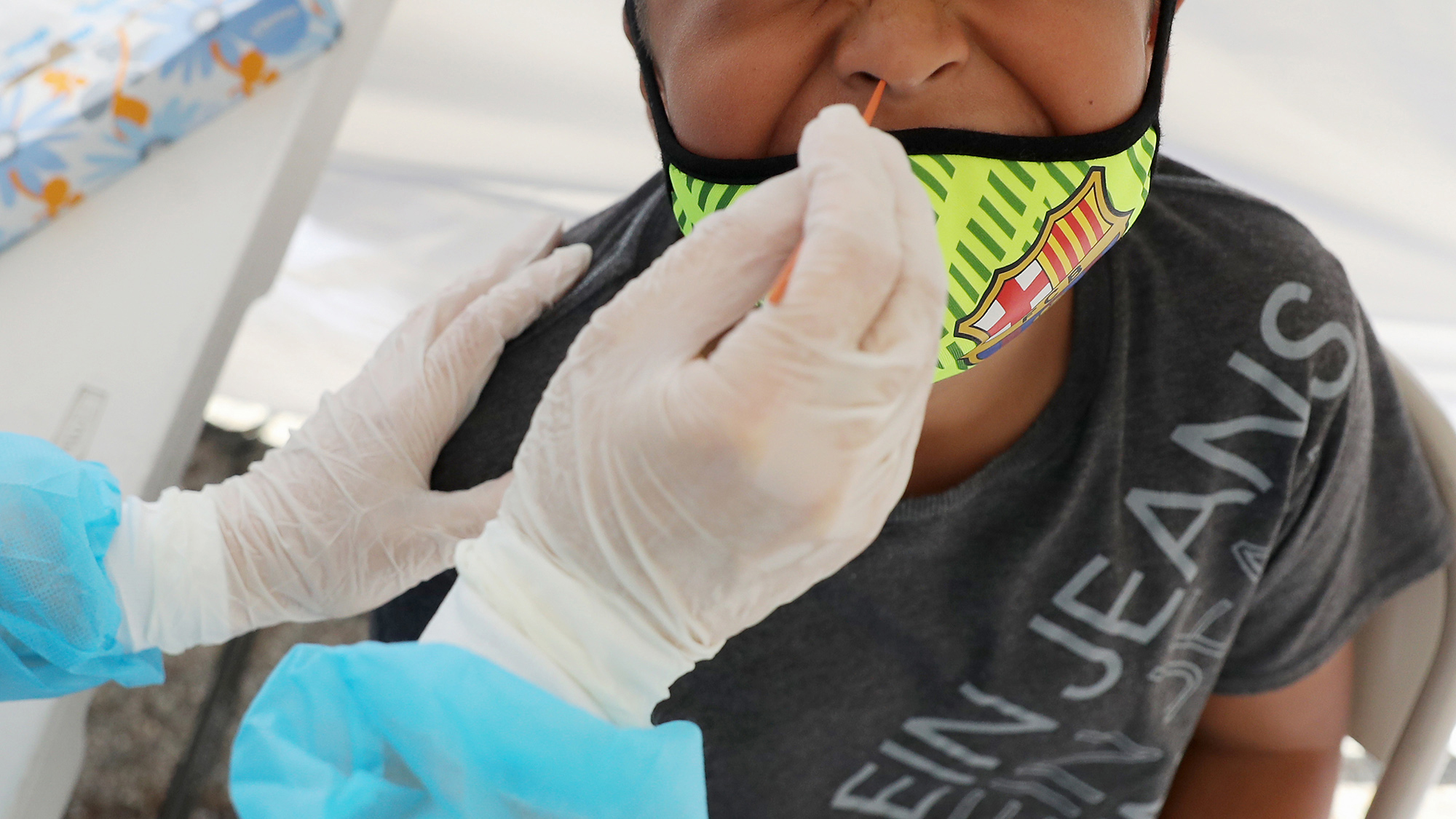 A boy receives a free Covid-19 test at a St. John's Well Child & Family Center mobile clinic set up outside Walker Temple AME Church in South Los Angeles amid the coronavirus pandemic on July 15.