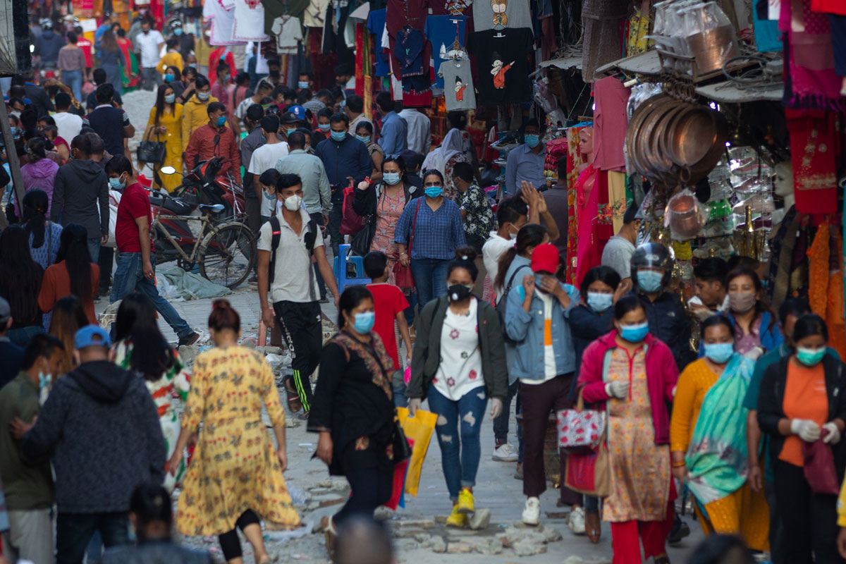 People wearing face masks as a preventive measure walk around a market in Kathmandu, Nepal, on October 9. As the Dashain festival season approaches, markets in the Nepalese capital are getting busy and crowded.