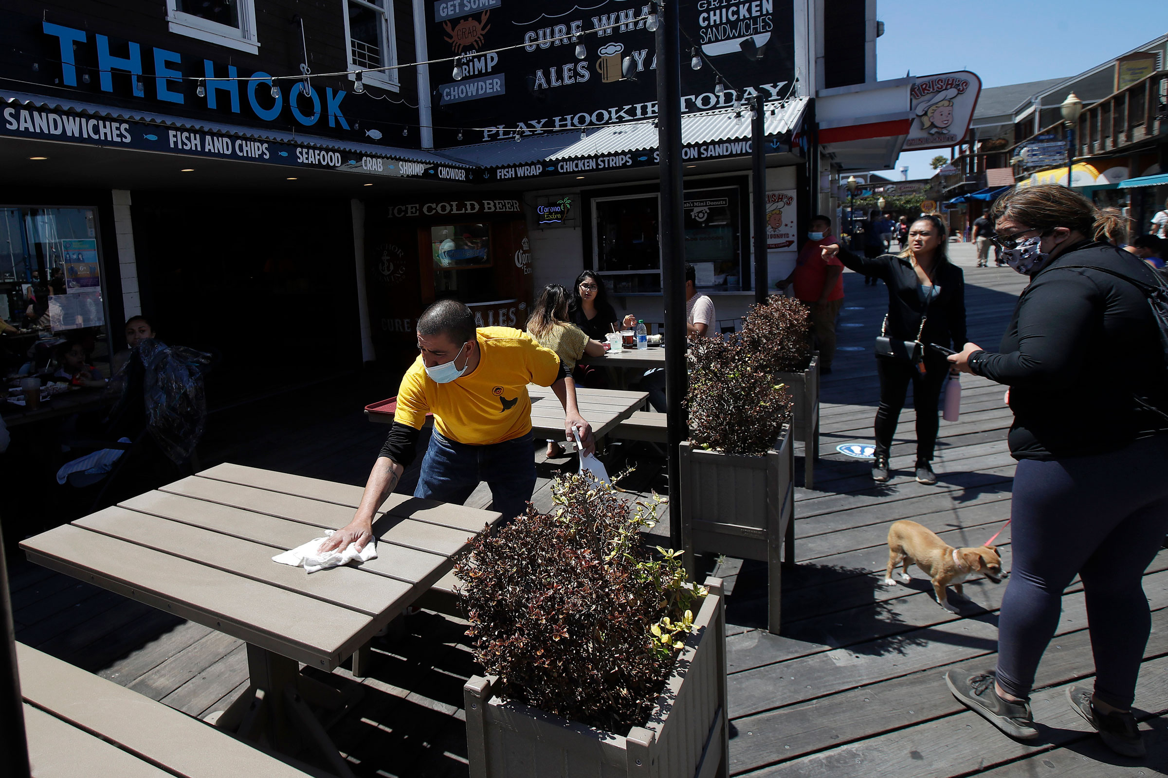 A man wears a face mask while cleaning an outdoor dining table at The Hook at San Francisco's Pier 39 on June 18.