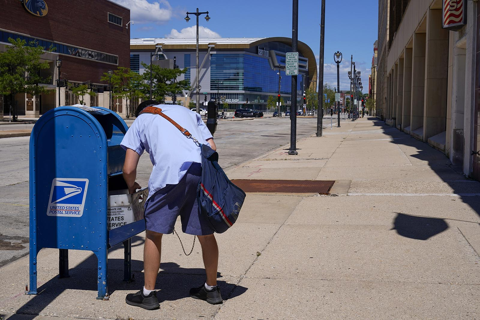 A postal worker empties a box near the Fiserv Forum on Tuesday, Aug. 18, in Milwaukee.