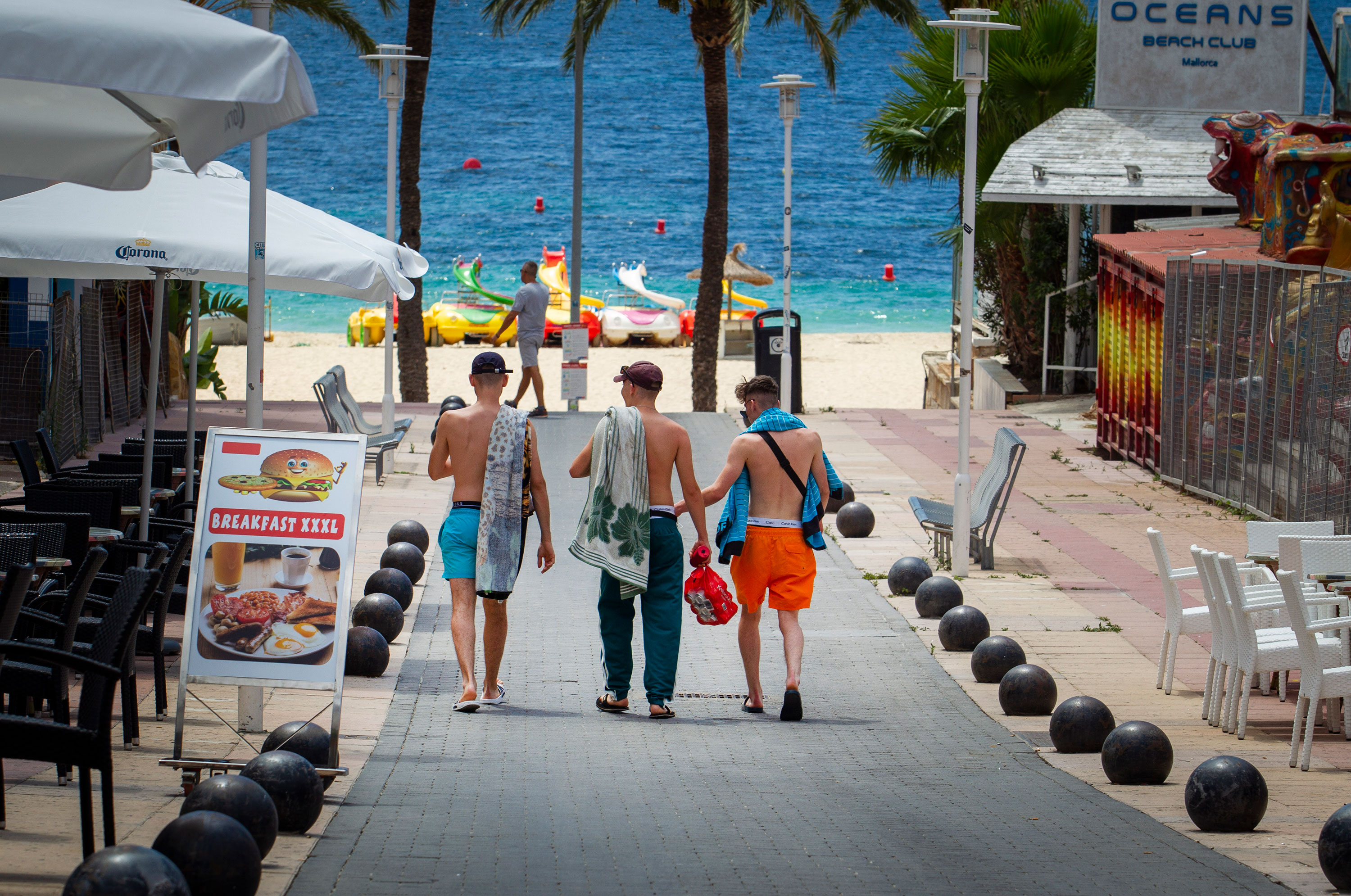 People walk towards a beach in Magaluf, on the Spanish island of Mallorca, on July 16.