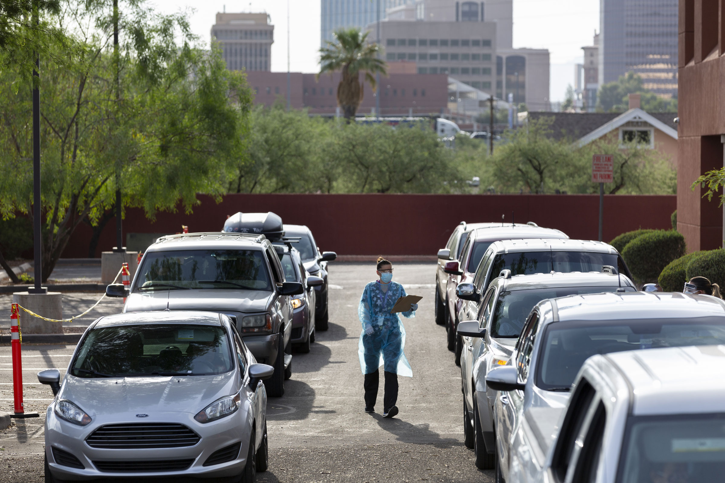 A health-care worker collects paperwork at a drive-thru testing site in Tucson, Arizona, on Monday.