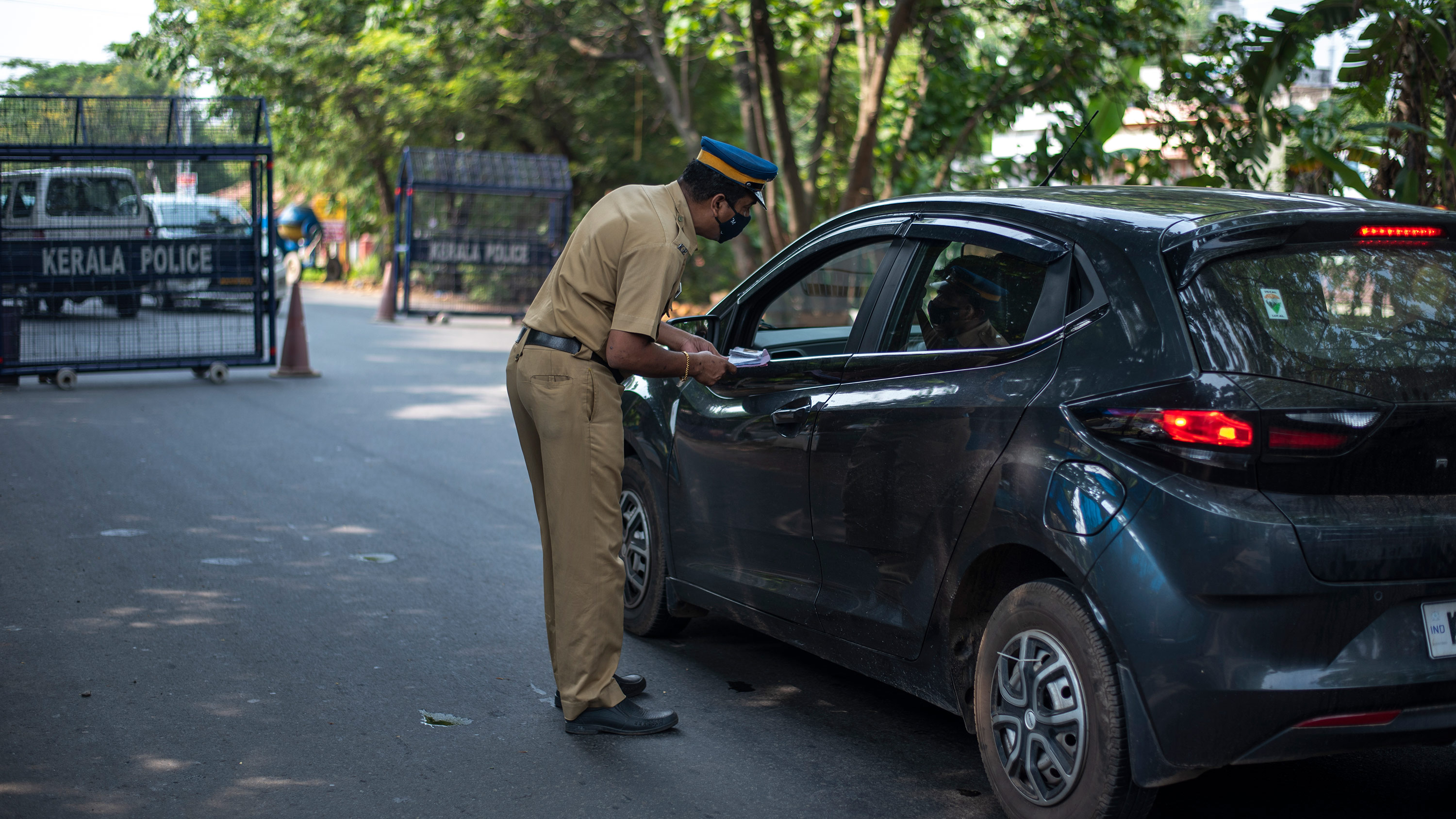 A policeman speaks with commuters during weekend restrictions imposed to curb of coronavirus in Kochi, India, on Sunday, April 25.