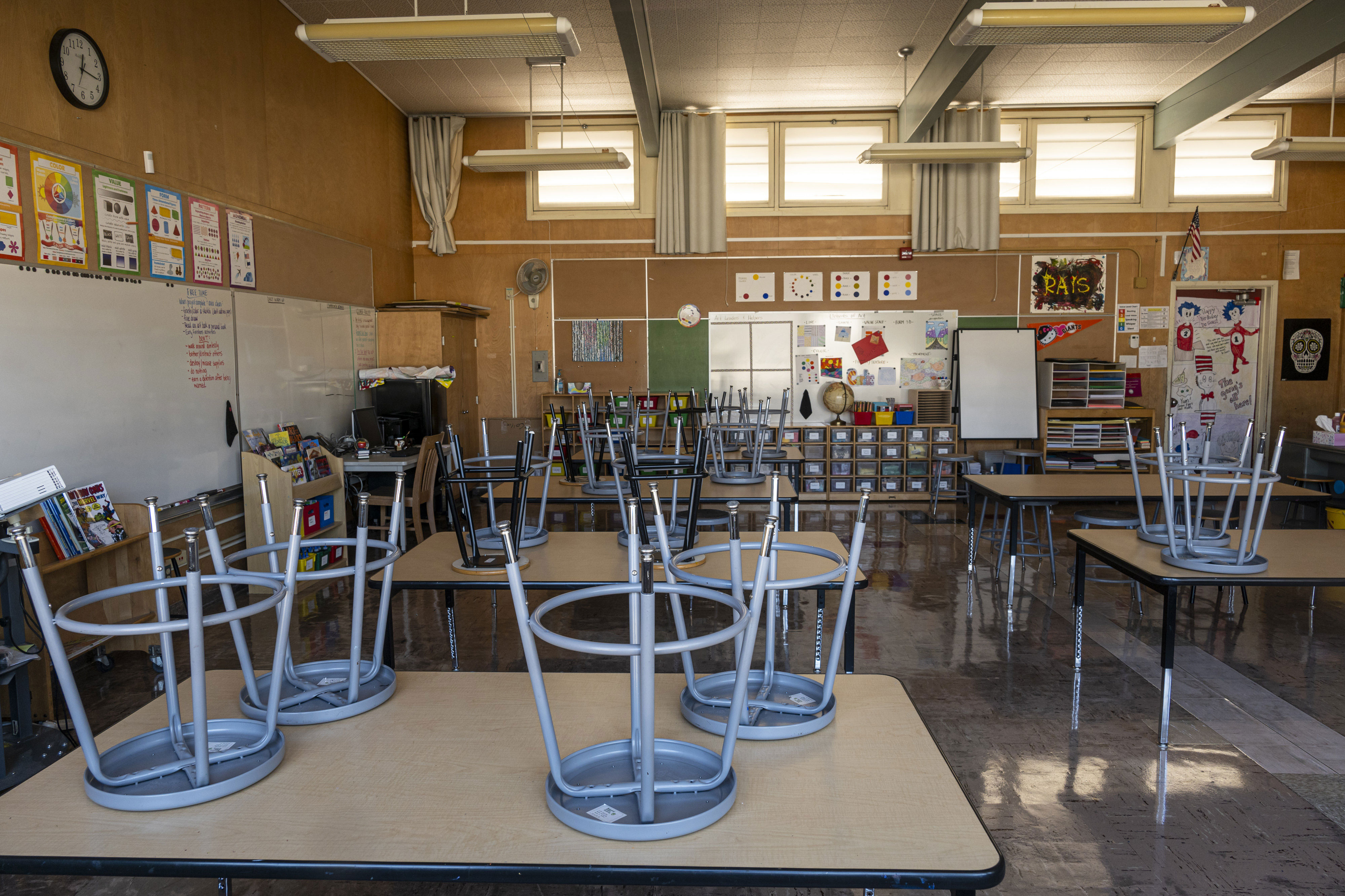 Stools are stacked on desks inside an empty classroom at Collins Elementary School in Pinole, California, on December 30, 2020.