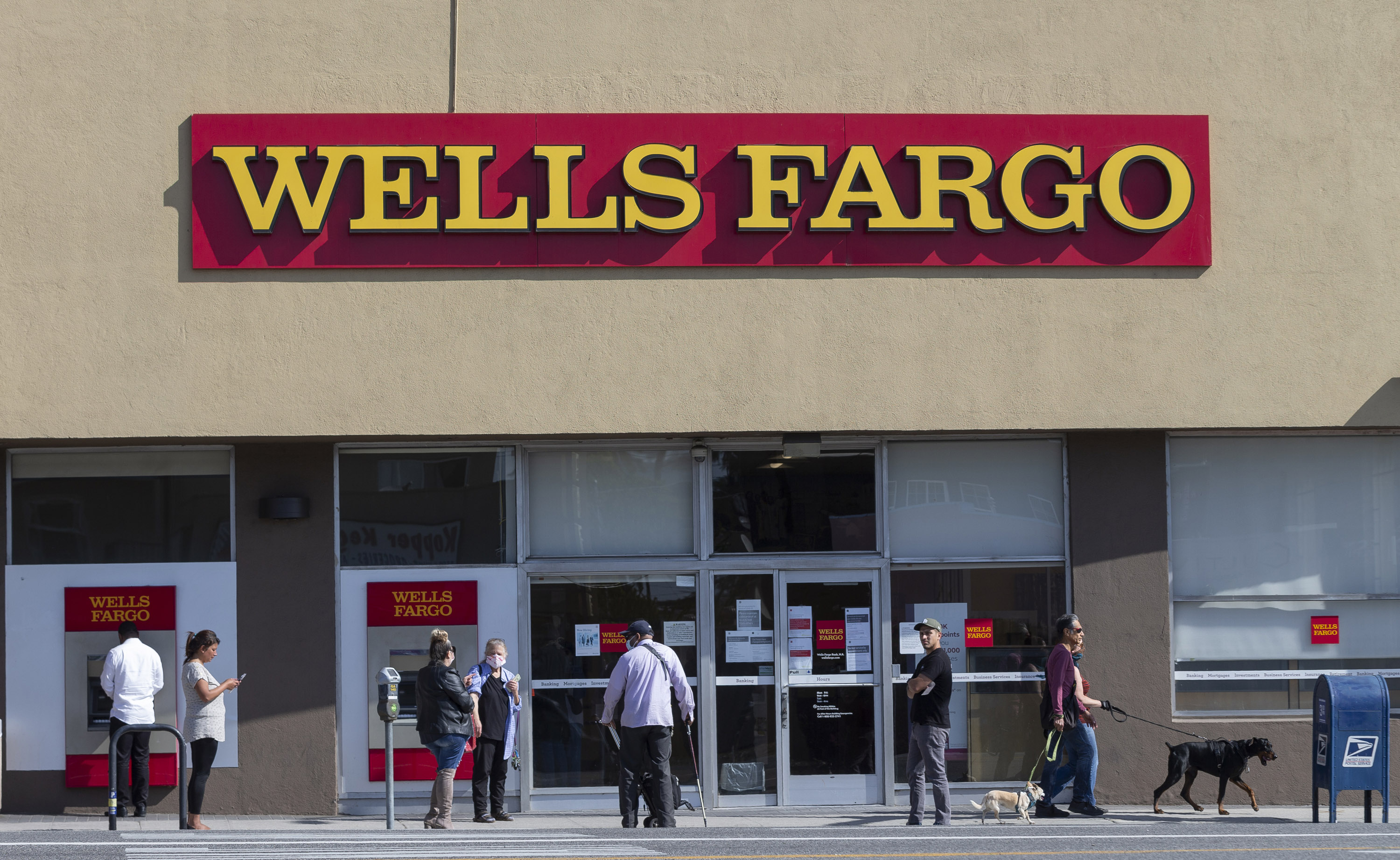 People stand outside a Wells Fargo branch in the Atwater Village neighborhood in Los Angeles on April 3.