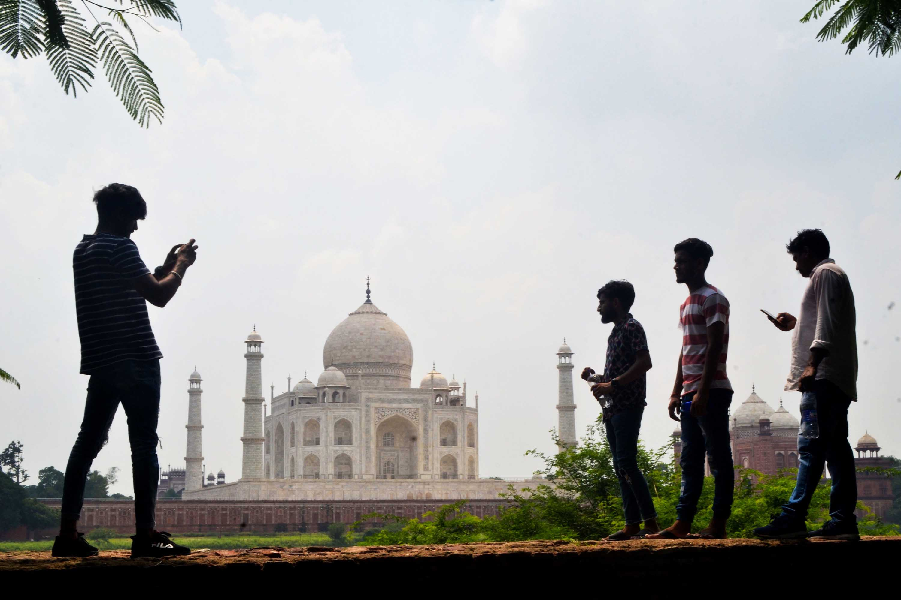 People take pictures near the Taj Mahal in Agra, India, on September 8, ahead of the landmark's reopening.