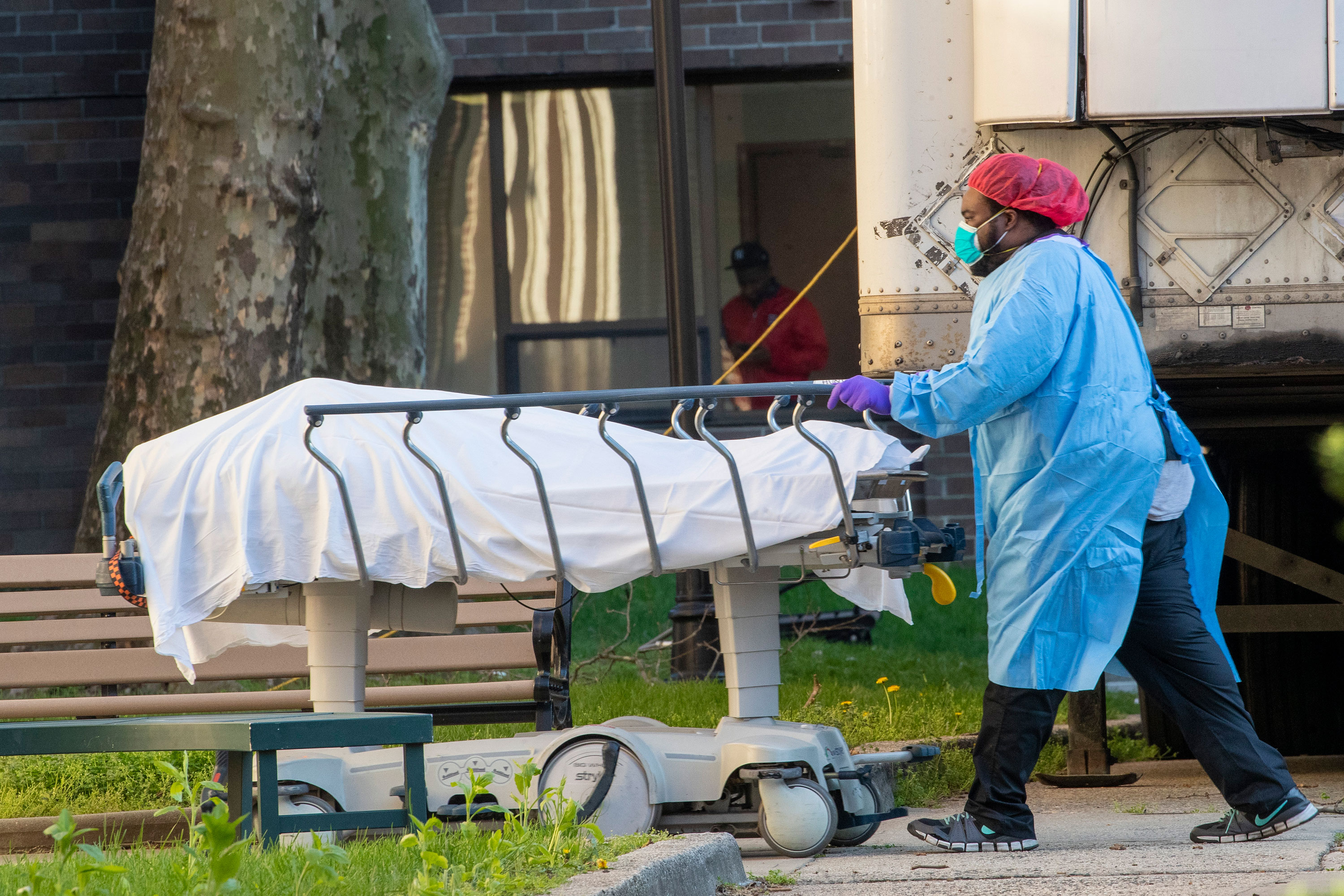 Medical personnel transport a body from a refrigerated container at Kingsbrook Jewish Medical Center, in the Brooklyn borough of New York on April 8.