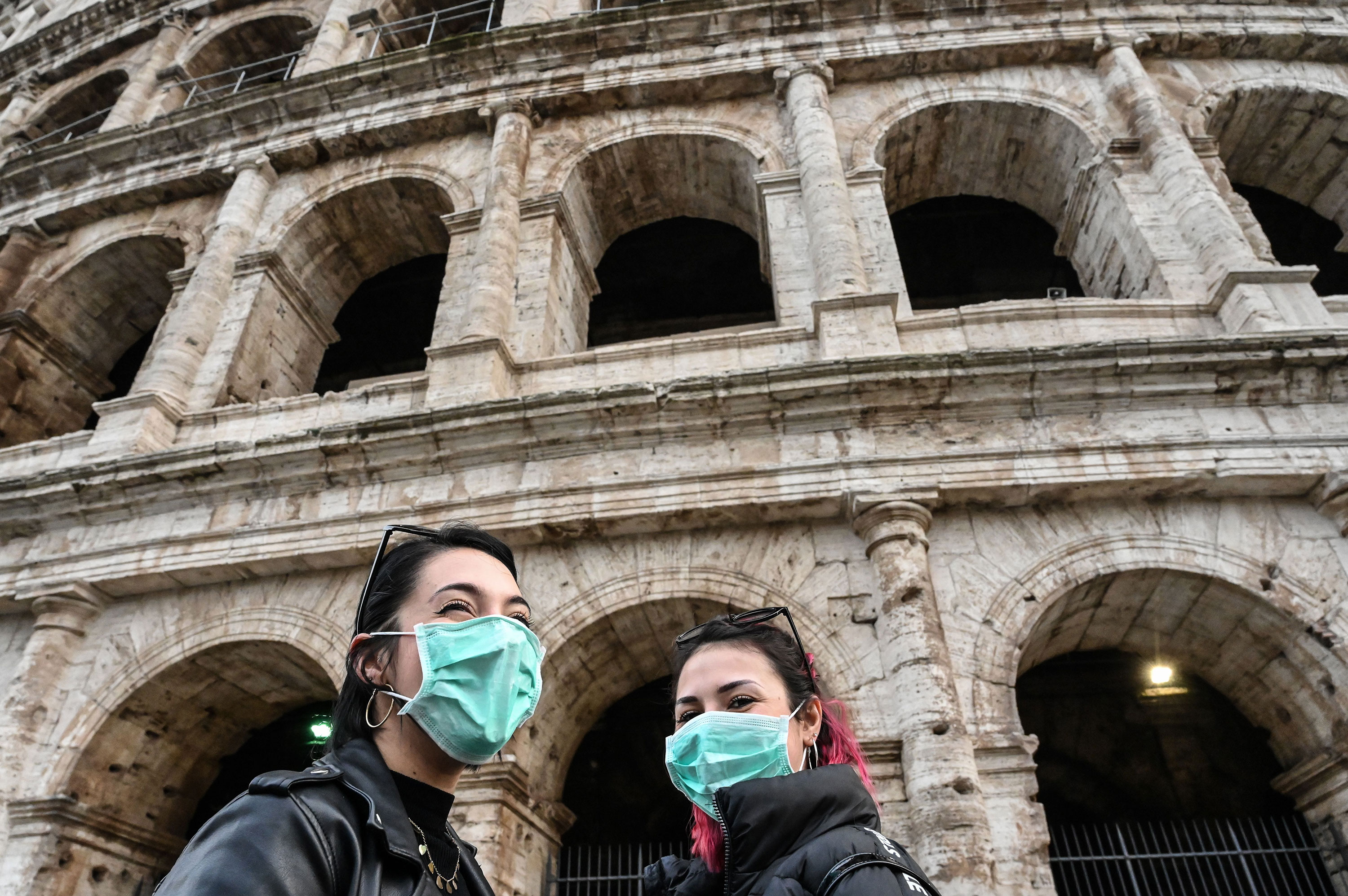 Tourists wear protective masks as they tour outside the Coliseum in Rome on January 31.