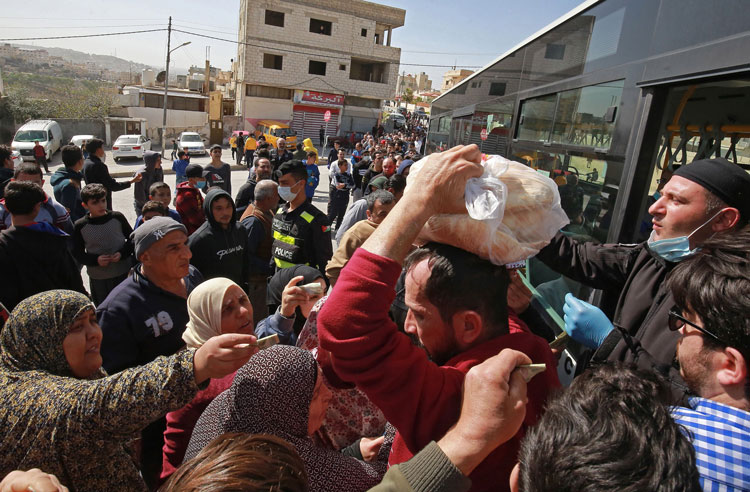 People queue to buy subsidized bread from a municipal bus in the Marka suburb in the east of Jordan's capital Amman on March 24.