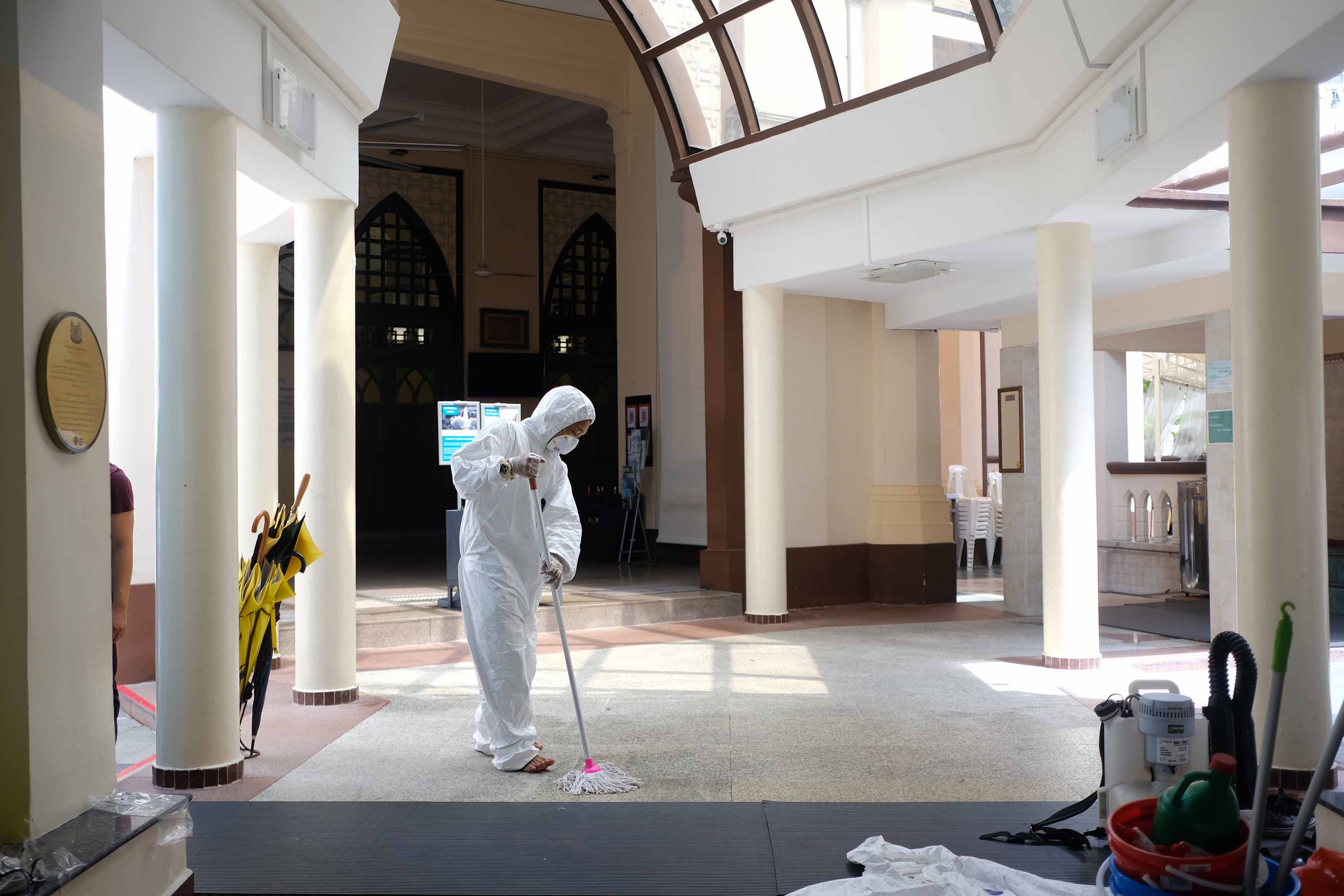 A working wearing protective gear mops the floor inside the Hajjah Fatimah mosque in Singapore on March 13.