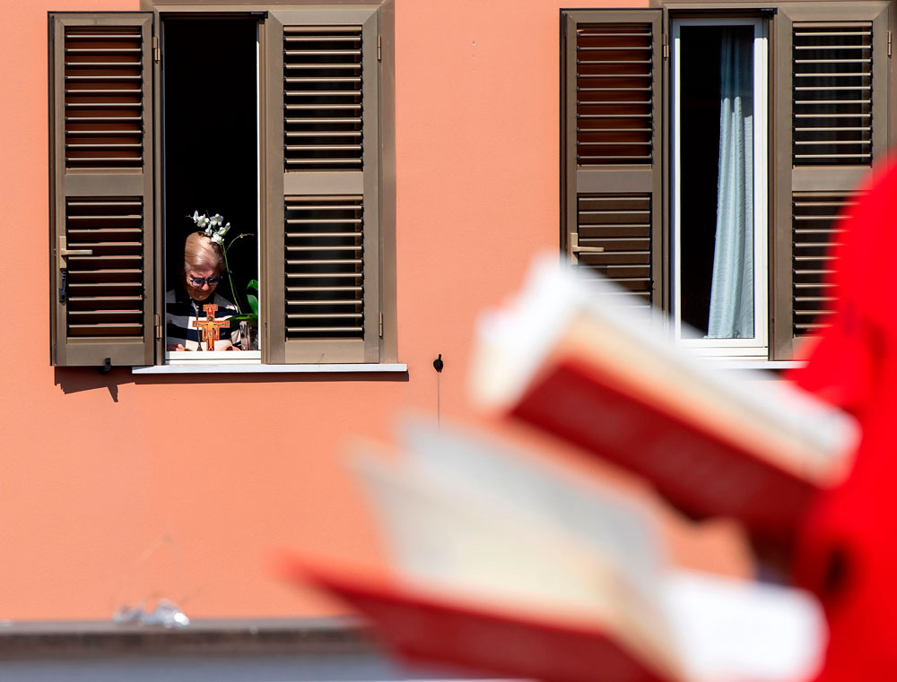 A resident watches from her apartment as Palm Sunday mass is celebrated on the rooftop of the San Gabriele dell'Addolorata church in Rome on April 5, during the country's lockdown.