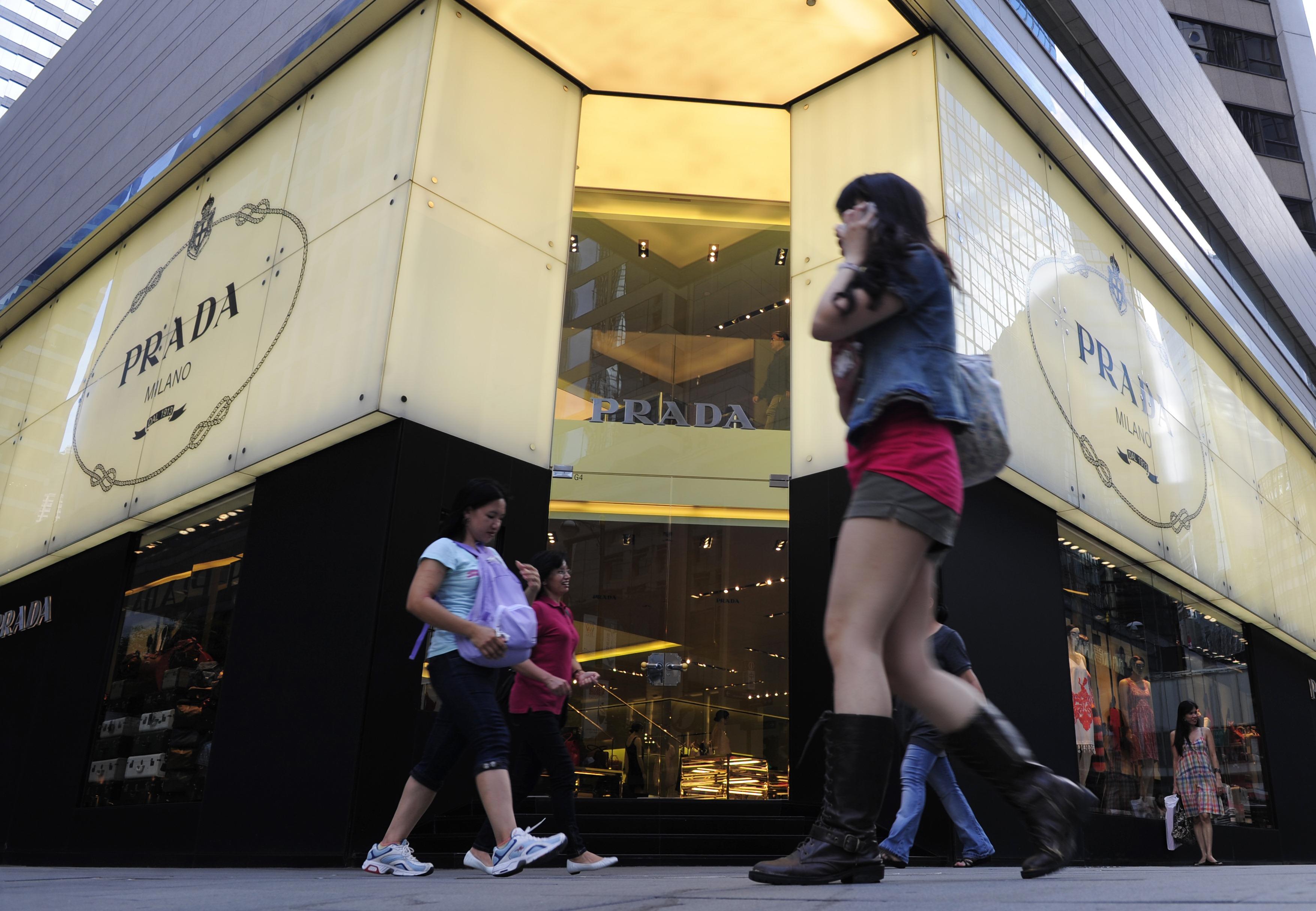Pedestrians walk past a Prada shop in Hong Kong.