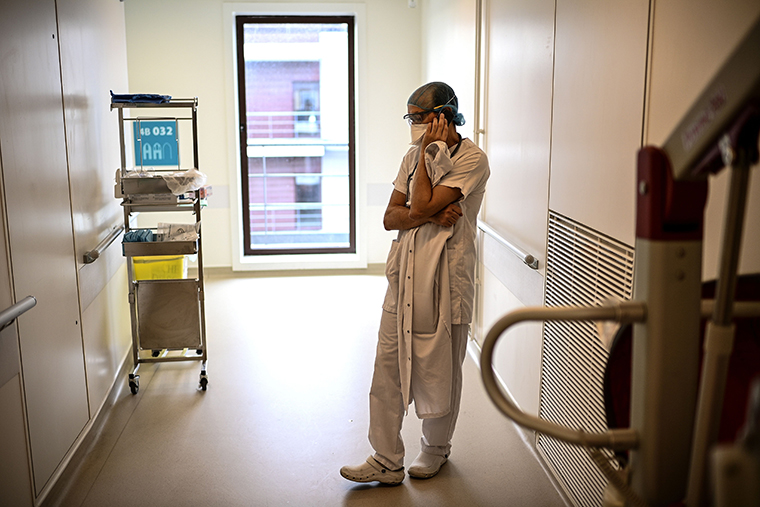 A doctor makes a phone call in a corridor of the infectious diseases unit of the Gonesse hospital before visiting a patient in Gonesse, north of Paris, on October 22, 2020.