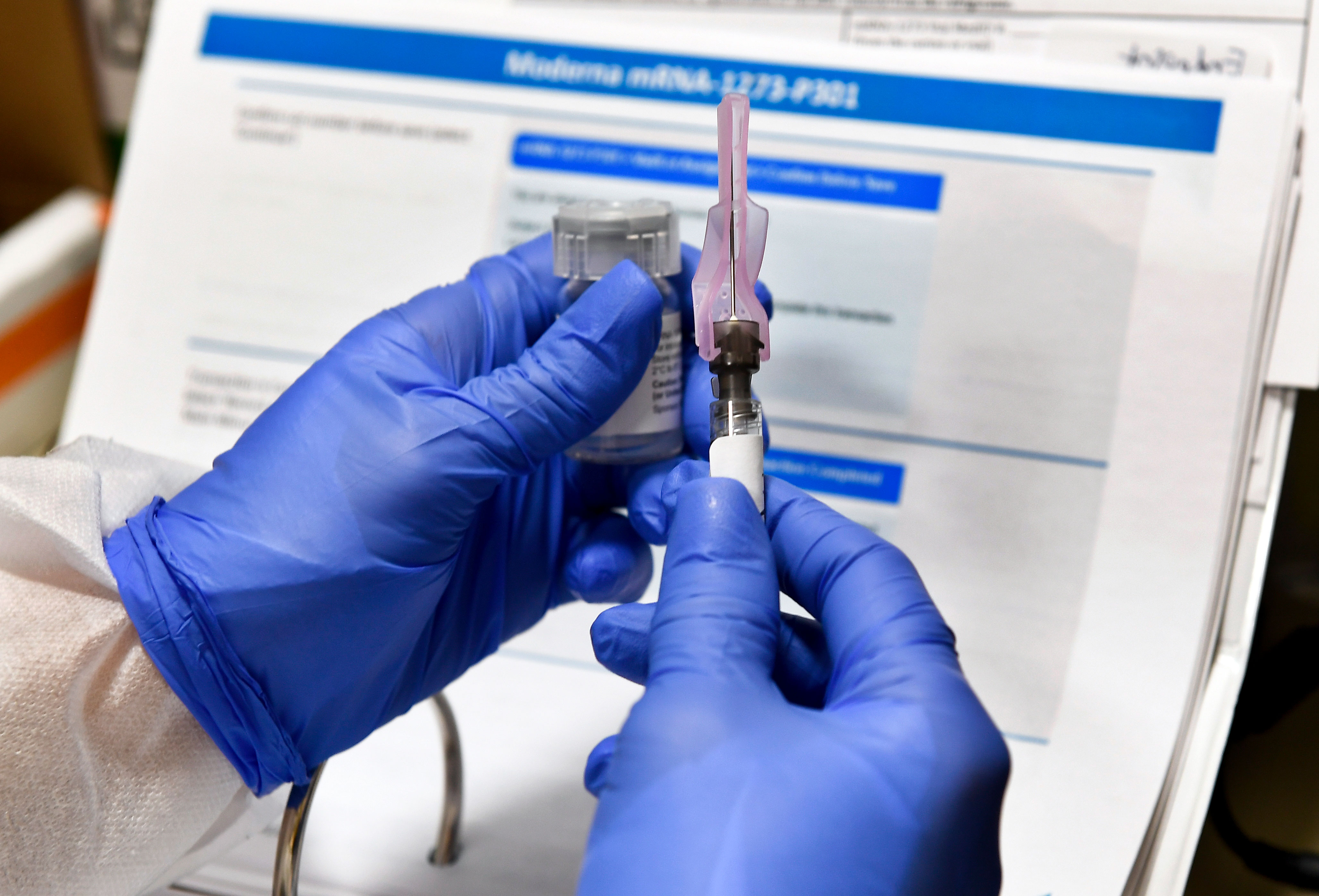 Nurse Kathe Olmstead prepares a syringe containing a Covid-19 vaccine,developed by the National Institutes of Health and Moderna on July 27 in Binghamton, New York.