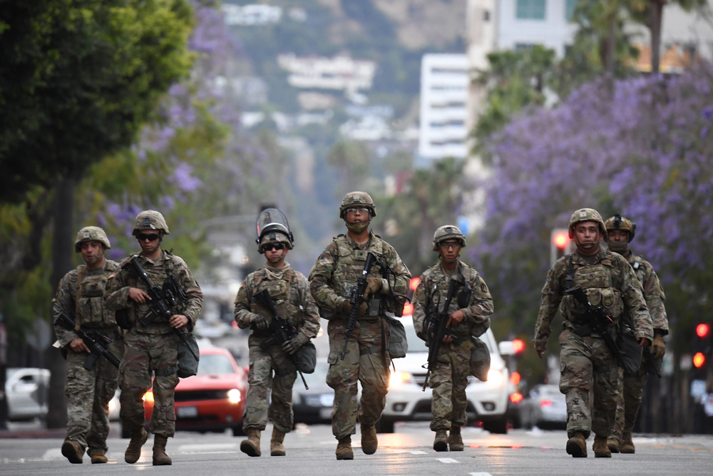 Armed National Guard soldiers patrol on Hollywood Boulevard on June 1 as peaceful protests and looting continue in Los Angeles County.