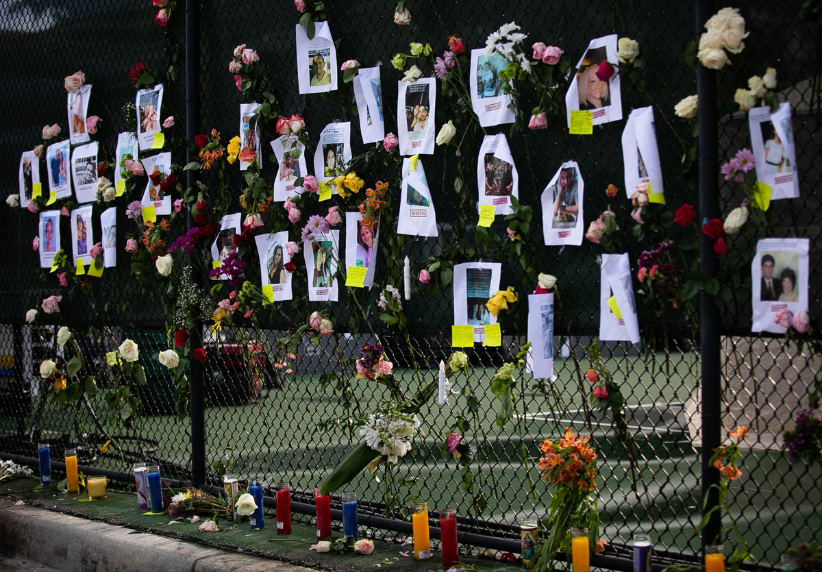 Photos of missing residents are posted at a makeshift memorial on June 26.