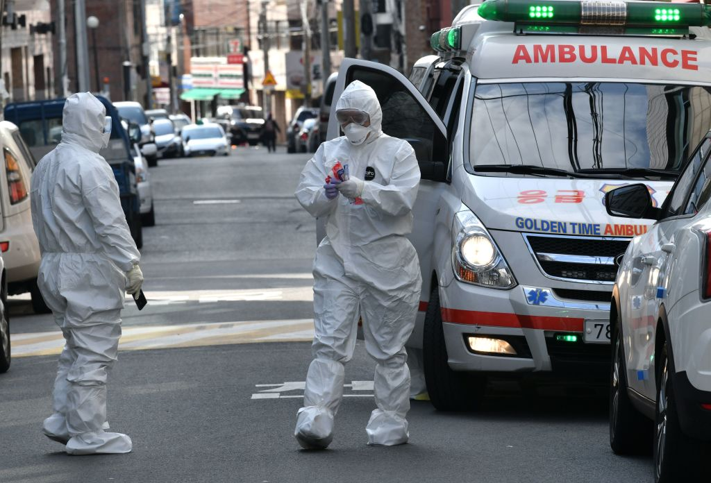 South Korean medical workers wearing protective gear carry samples as they visit the residence of people with suspected symptoms of the  coronavirus, near the Daegu branch of the Shincheonji religious group on February 27, 2020. (Photo by JUNG YEON-JE/AFP via Getty Images)