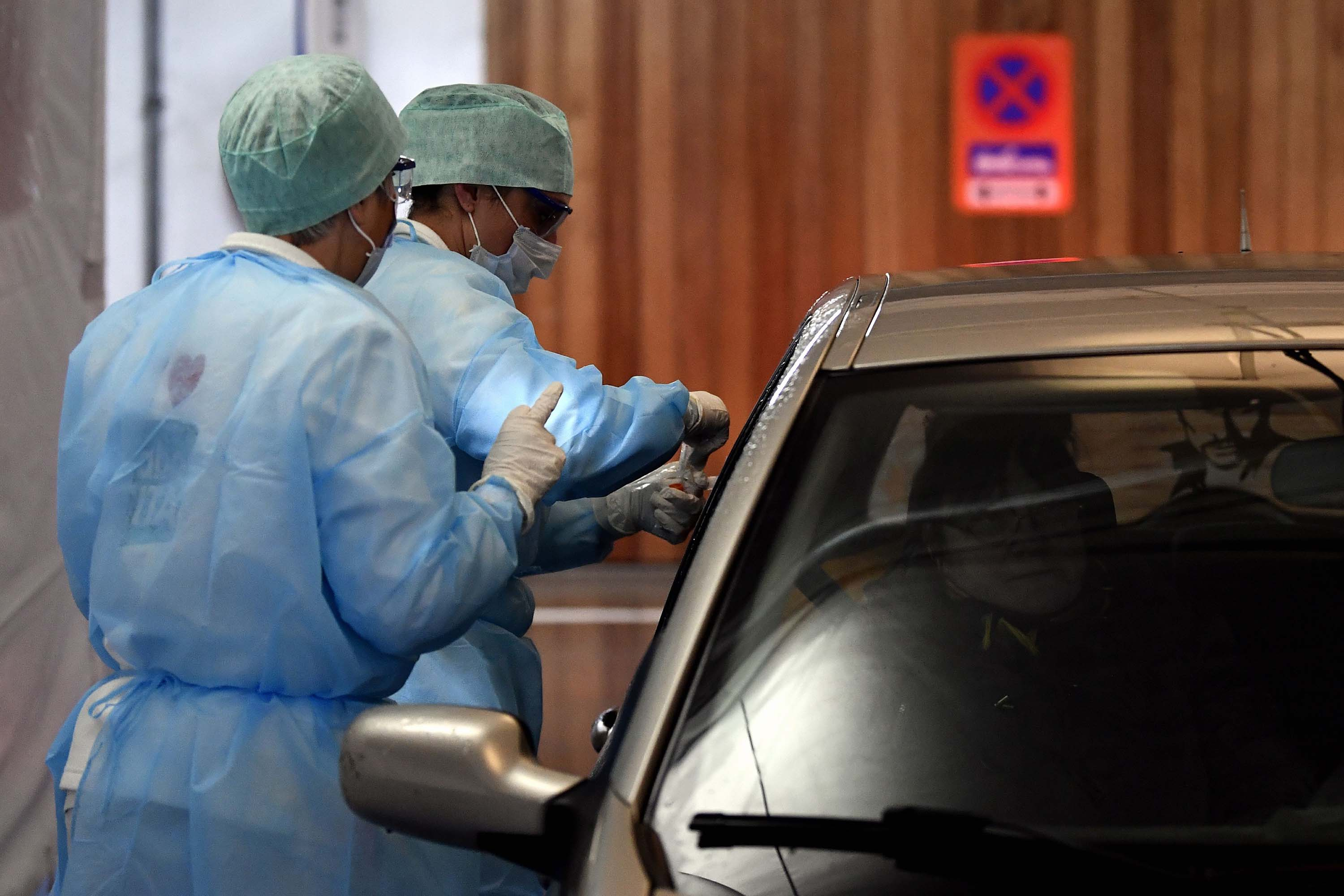 Medical staff take samples from a driver at a drive-through coronavirus testing facility, at hospital in Liege, Belgium, on Tuesday.