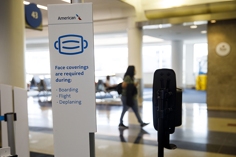 A sign reminds travelers to wear face coverings displayed at an American Airlines Group Inc. boarding gate at Los Angeles International Airport in Los Angeles, California, U.S., on Thursday, Oct. 1, 2020.