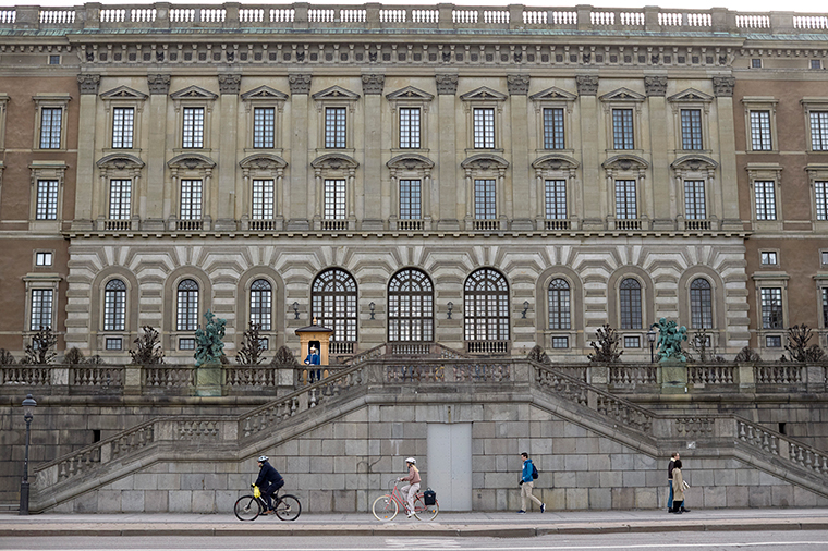 People pass by the Royal Palace in Stockholm, Sweden, on Wednesday, April 8. Swedish authorities have advised the public to practice social distancing because of the coronavirus pandemic, but still allow a large amount of personal freedom, unlike most other European countries.