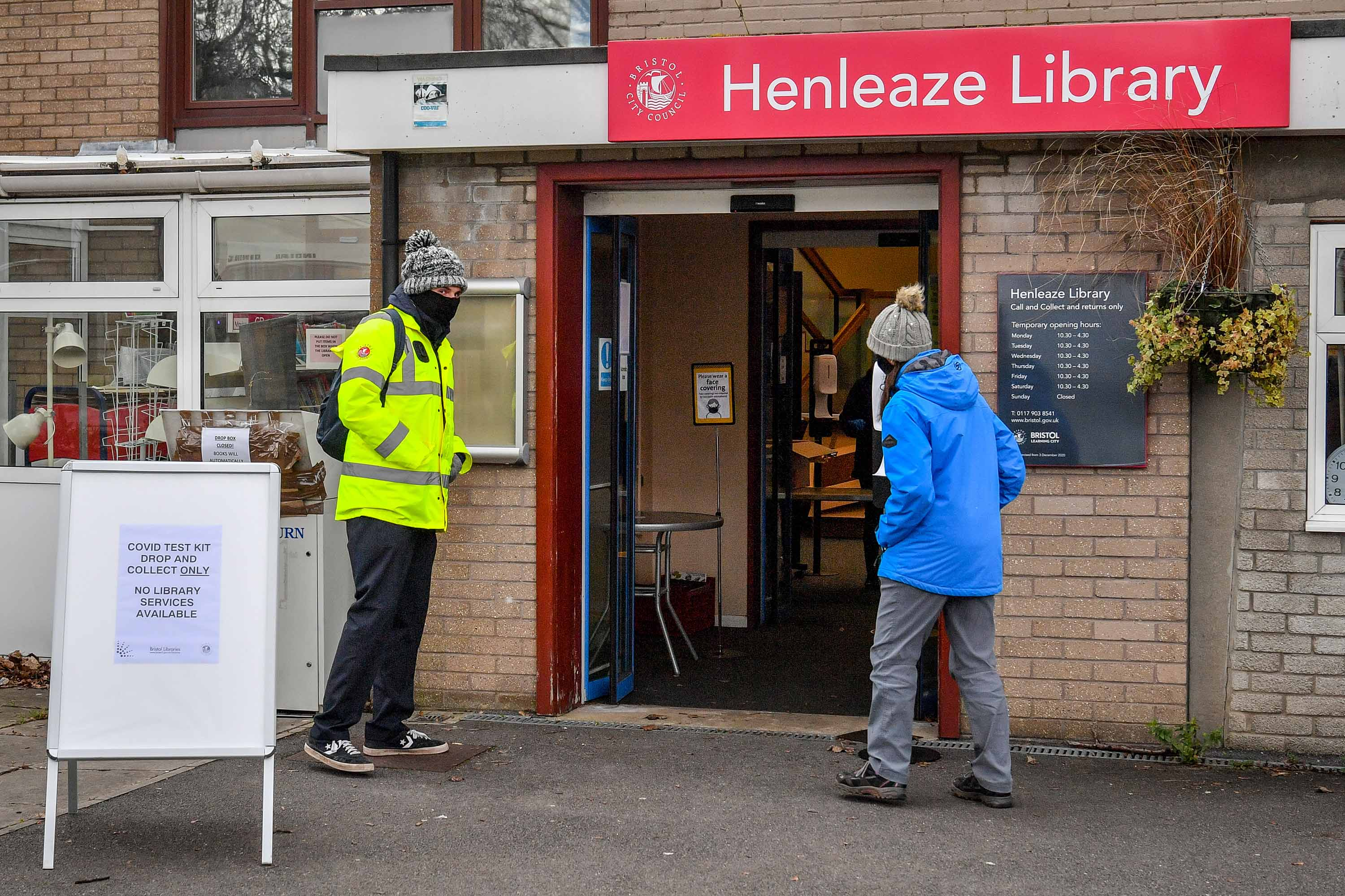 People wait outside a coronavirus surge testing center at a library in Bristol, England, on February 9, following the identification of a mutated variant in the region.
