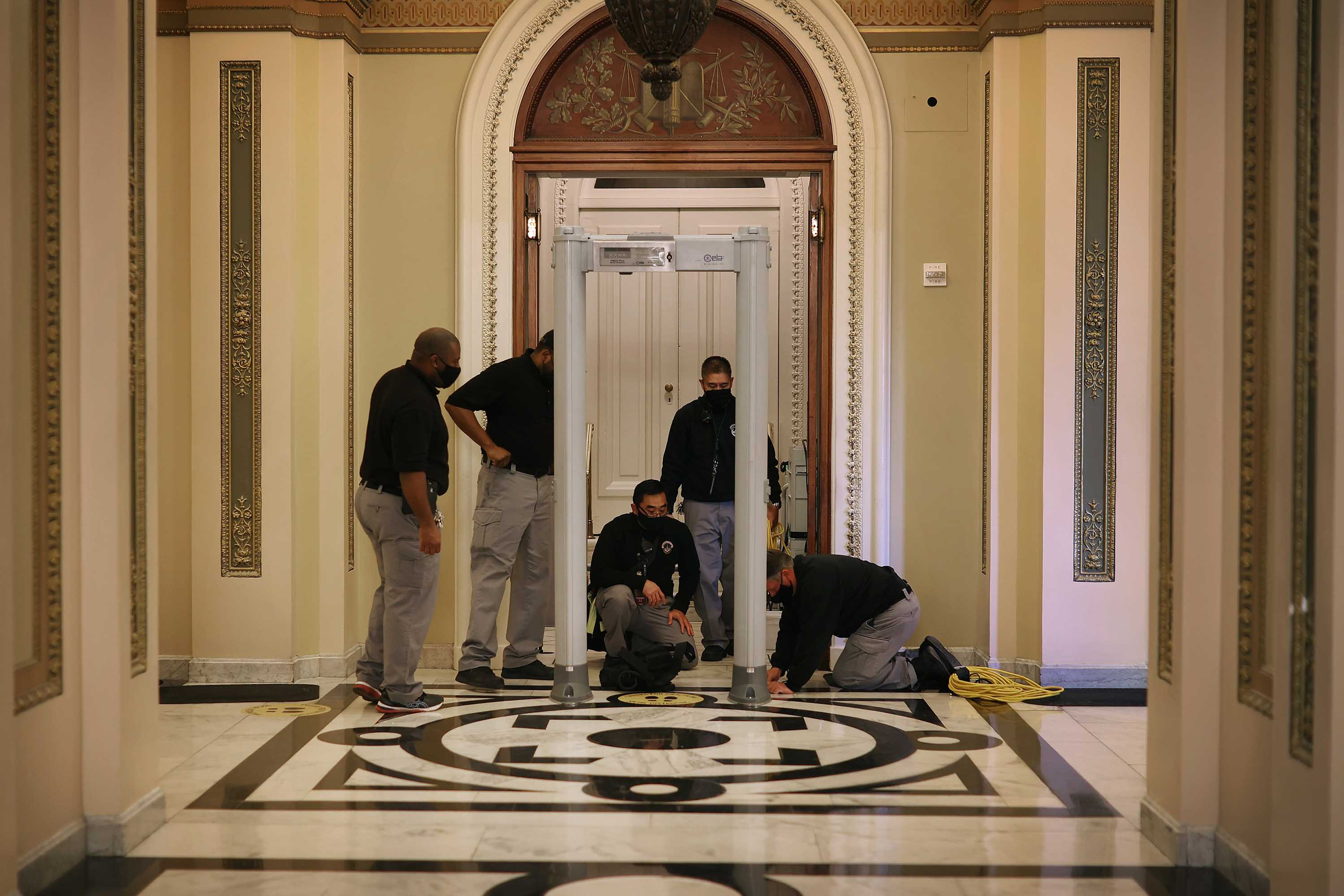 U.S. Capitol Police install a metal detector outside the House of Representatives Chamber at the US Capitol in Washington, DC, on January 12.